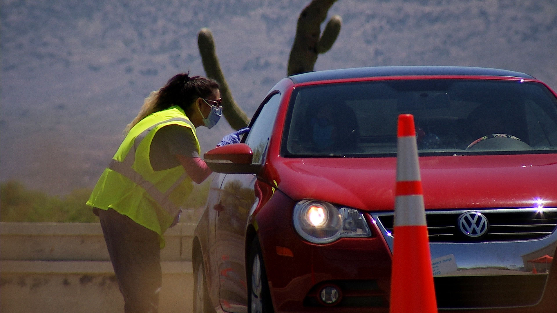 A woman speaks to someone in a vehicle seeking a COVID-19 test at a drive-thru testing site set up at Walgreens in Tucson on April 21, 2020.