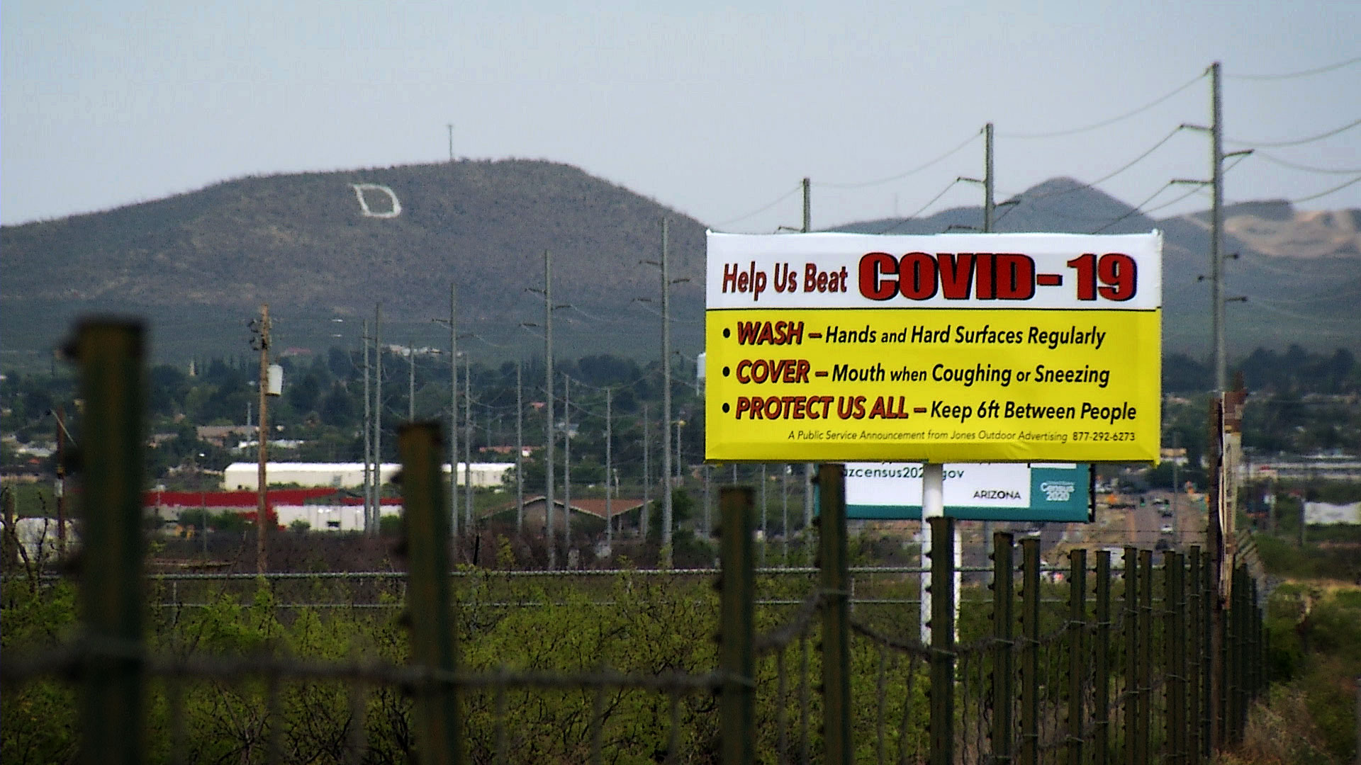 A sign urging protective measures against the novel coronavirus along a road in Douglas, Arizona. April 2020.