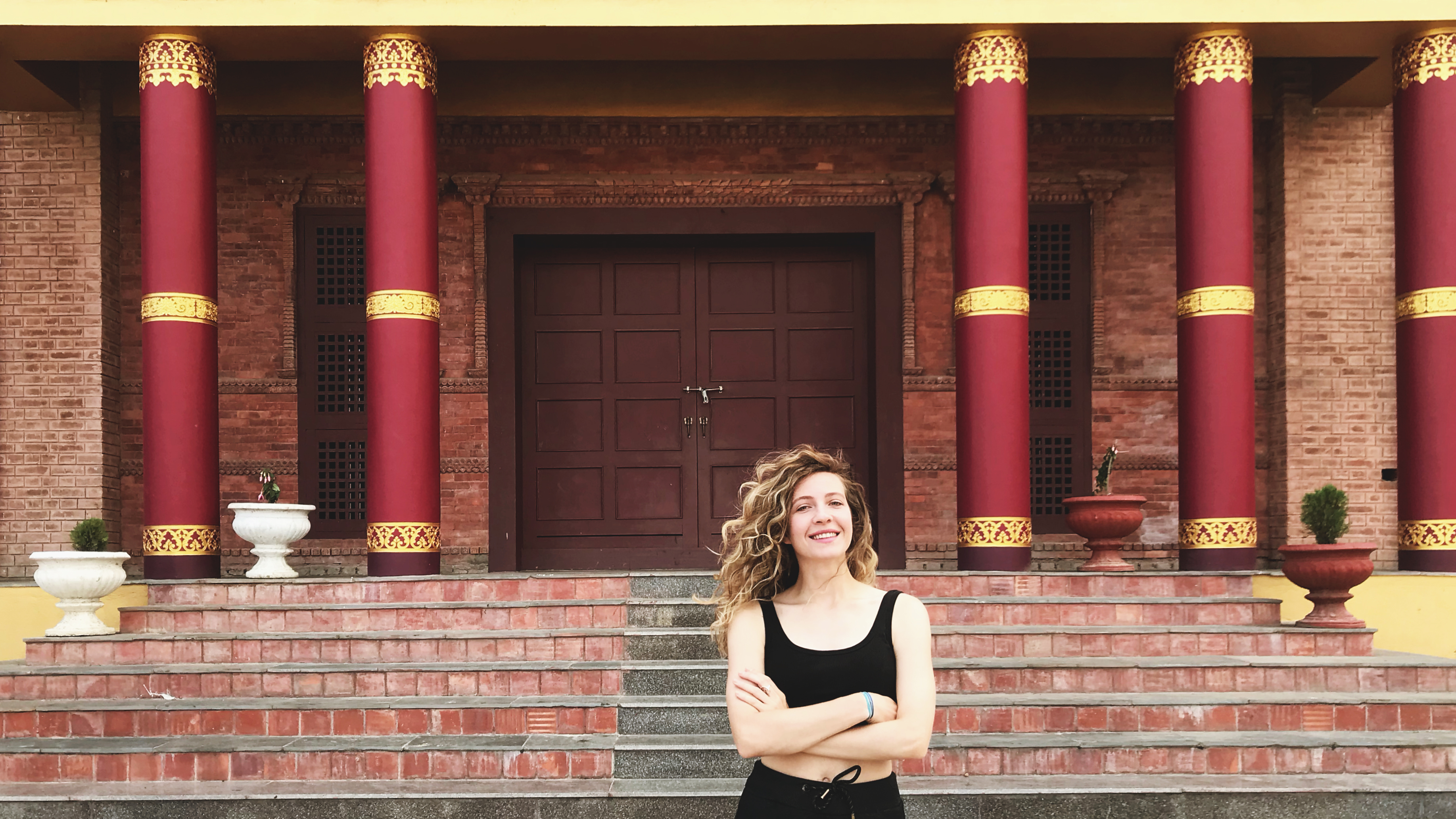 Katya Demidkova in front of the Sharminub monastery, near Kathmandu, in Nepal. During the COVID-19 pandemic, she is teaching English to the boys who live there, studying to become monks.