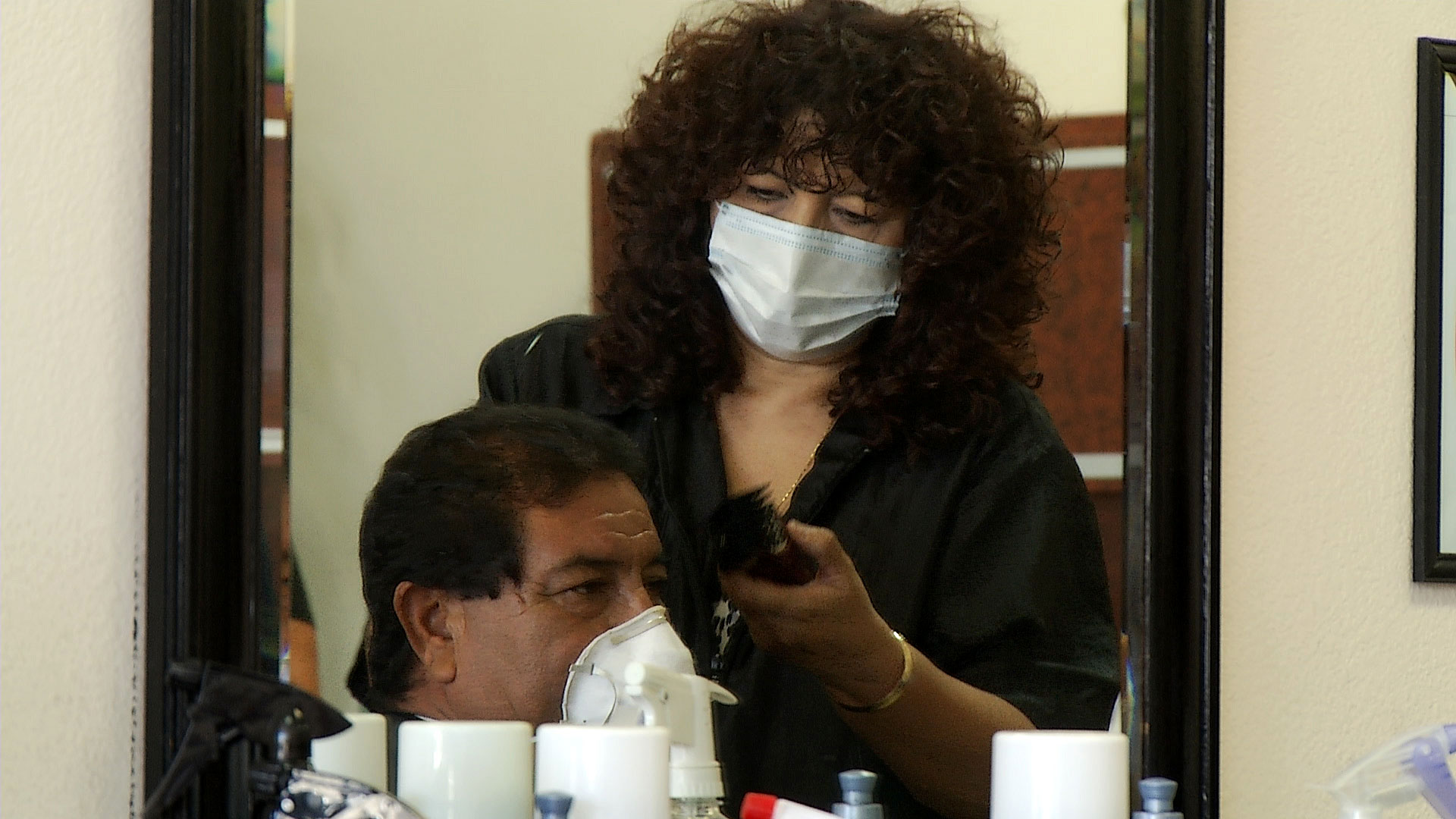 Both a customer and stylists wear face masks during a hair cut at Eclips Cuts Salon in Tucson on May 12, 2020. The salon reopened when Arizona eased COVID-19-related restrictions that had ordered barbers and salons to close.