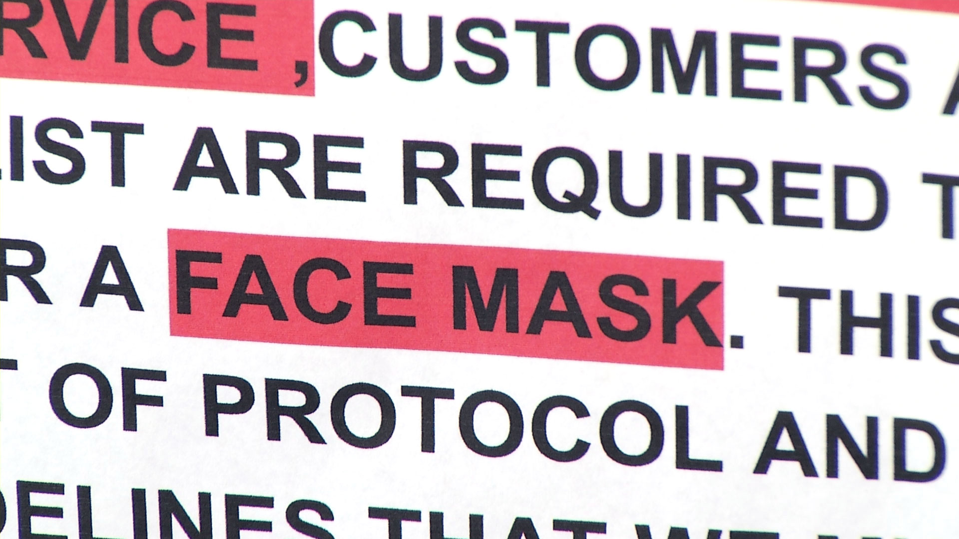 A close up of a message at Eclips Cuts Salon in Tucson notifies customers that face masks are required to enter the business. May 12, 2020.