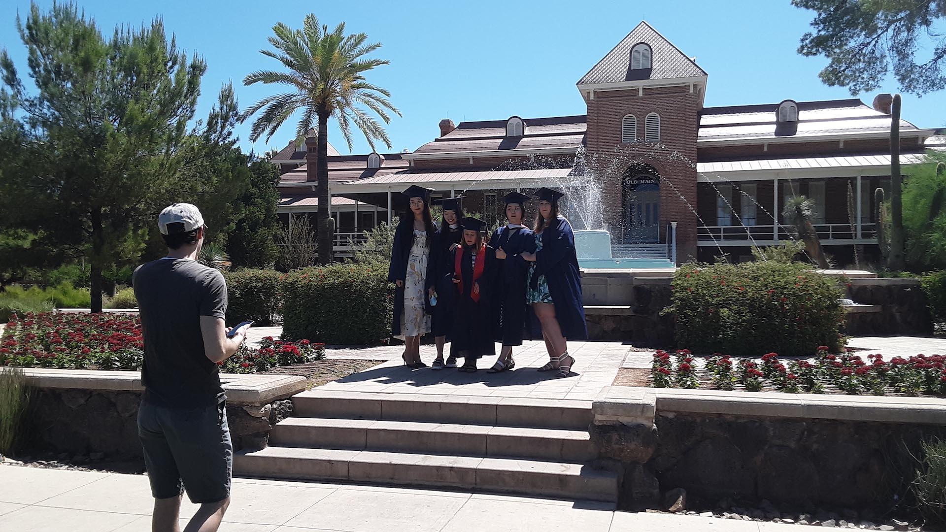 Spring 2020 University of Arizona graduates pose for photos at Old Main.