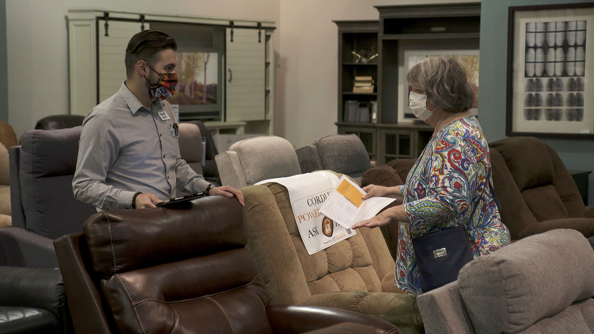 A sales associate and customer both wear masks as they interact at Sam Levitz in Tucson on May 19, 2020.