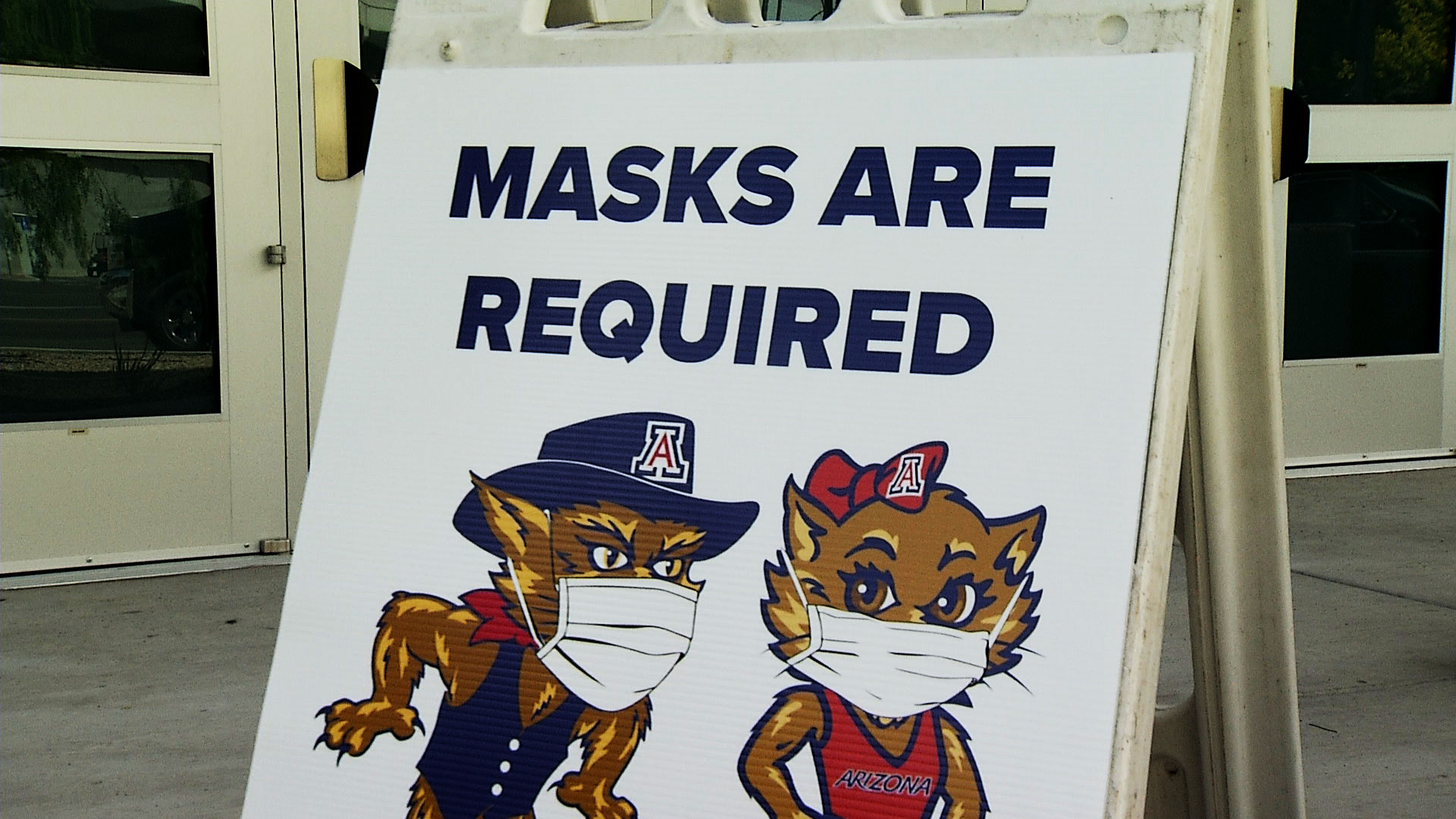 A sign featuring University of Arizona mascots lets people know face masks are required outside of the entrance to the facility where the university is collecting samples for its antibody testing initiative. April 30, 2020.