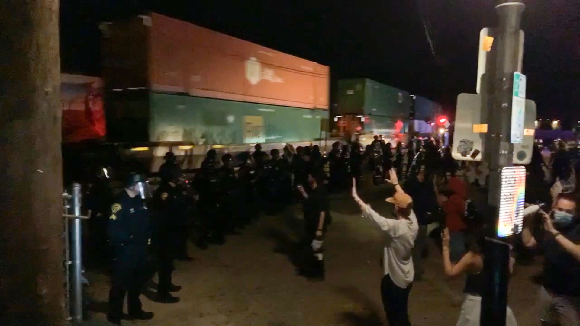 As a train passes, marching demonstrators raise their hands after being stopped by police near downtown Tucson Saturday night in this still image from a video, as protests over the death of George Floyd spread across the country.