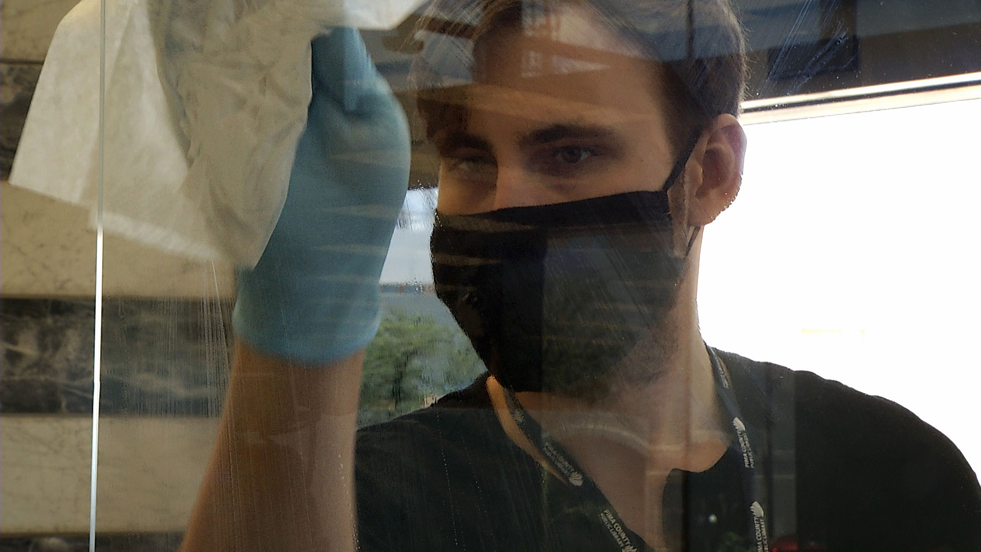A worker at the Pima County Public Library's downtown branch sanitizes a plexiglass shield on May 29, 2020.