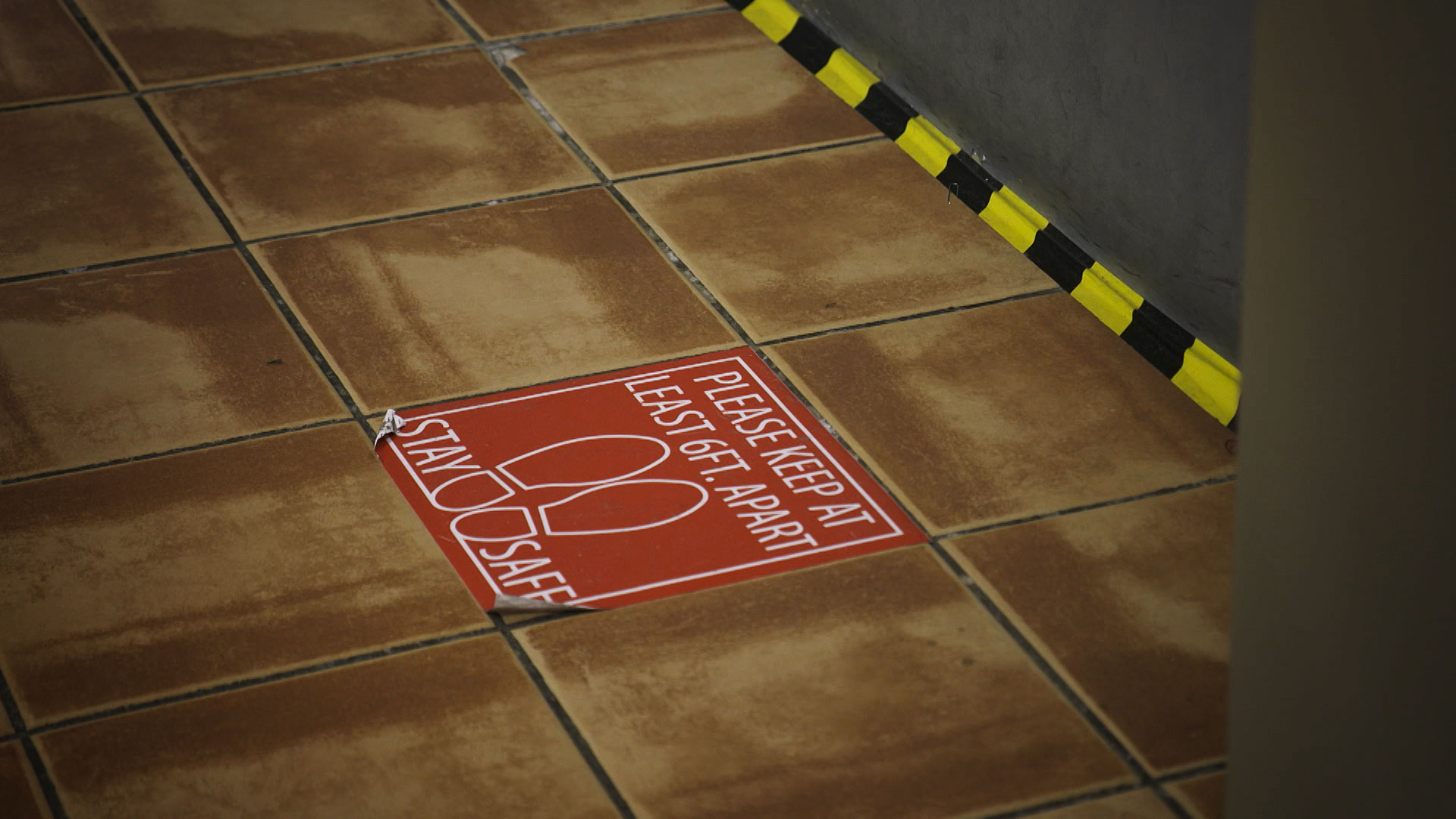 A sticker on the ground notifies customers where to stand in order to maintain social distancing at Sam Levitz Furniture Warehouse. May 2020.
