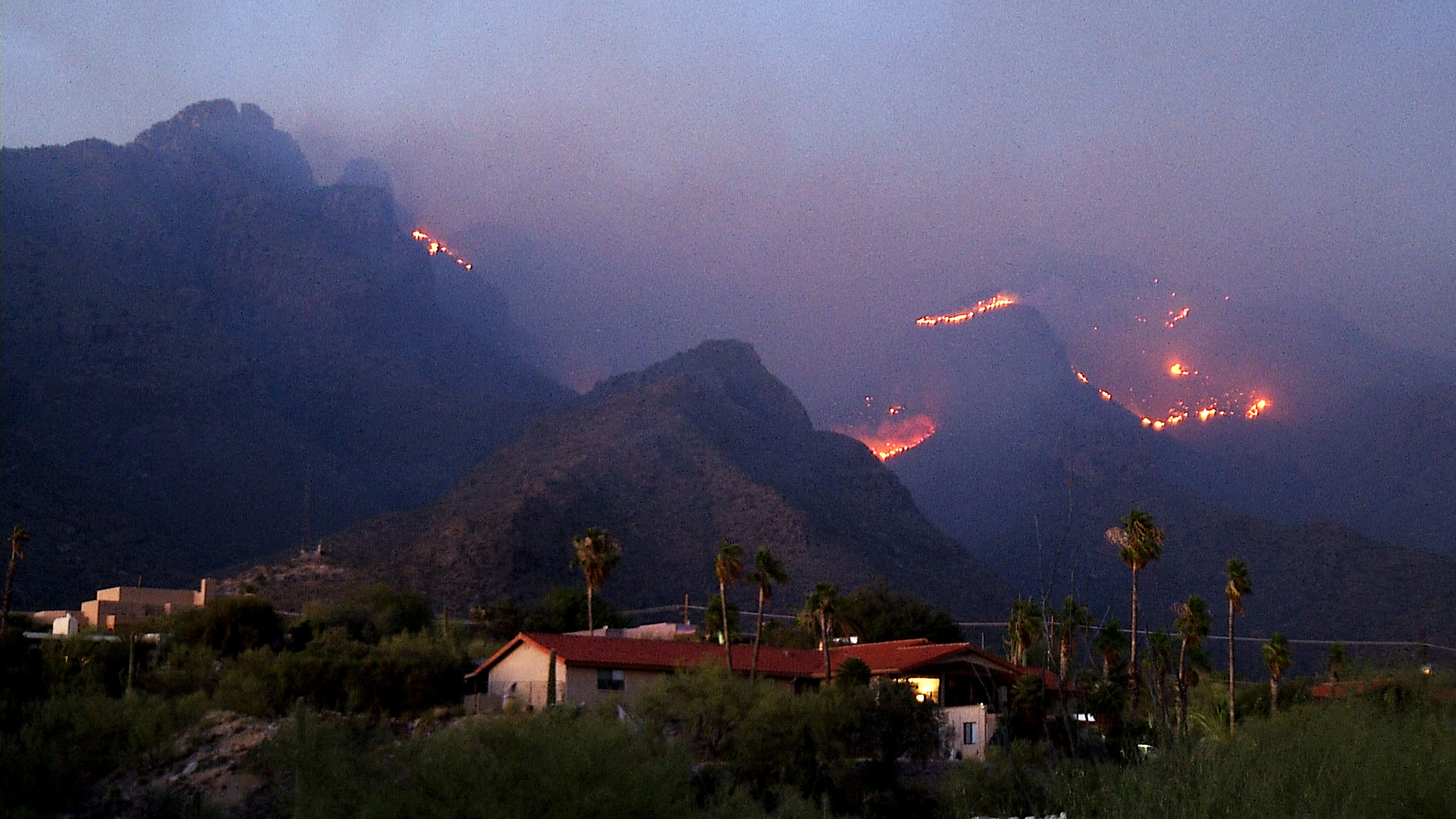 With residences in the foreground, the Bighorn Fire burns in the Santa Catalina Mountains on June 10, 2020.
