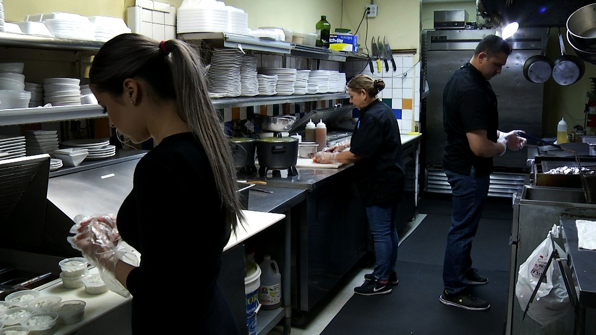The owner of Shish Kebab House of Tucson (center) and employees work in the kitchen to fill to-go orders. The restaurant saw a sharp decline in business when it had to halt dine-in service during the Arizona's stay-at-home order. April 2020.
