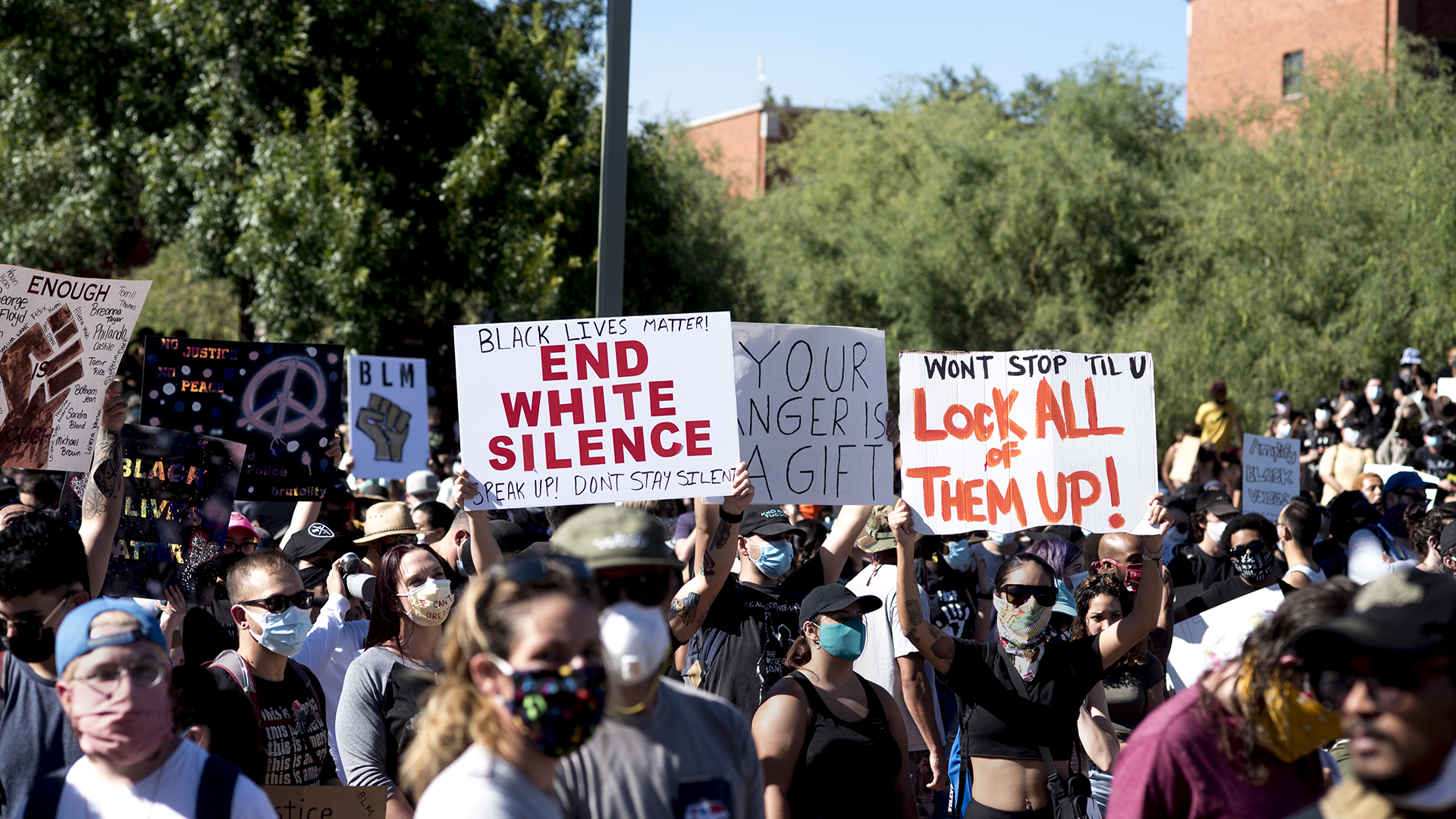 Demonstrators hold up signs recognizing George Floyd and condemning police brutality during and Black Lives Matter Tucson event on June 6, 2020.