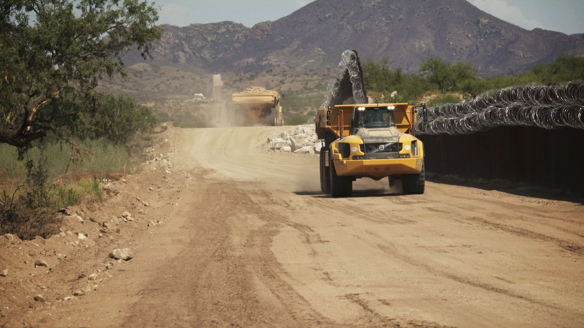 Construction trucks drive along the border wall in Sasabe on July 13, 2020.