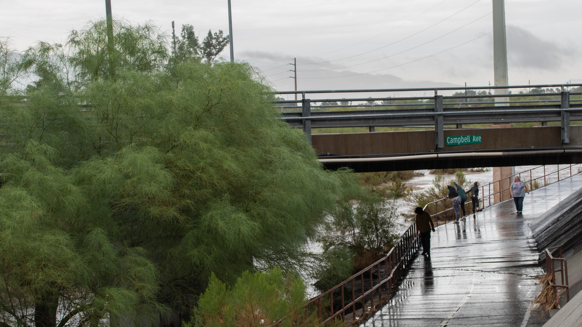 People stand under the Campbell Avenue bridge to watch the Rillito  run after a monsoon storm,  July 23, 2020. Rains cooled the city, and helped finish the job putting out the Bighorn Fire.