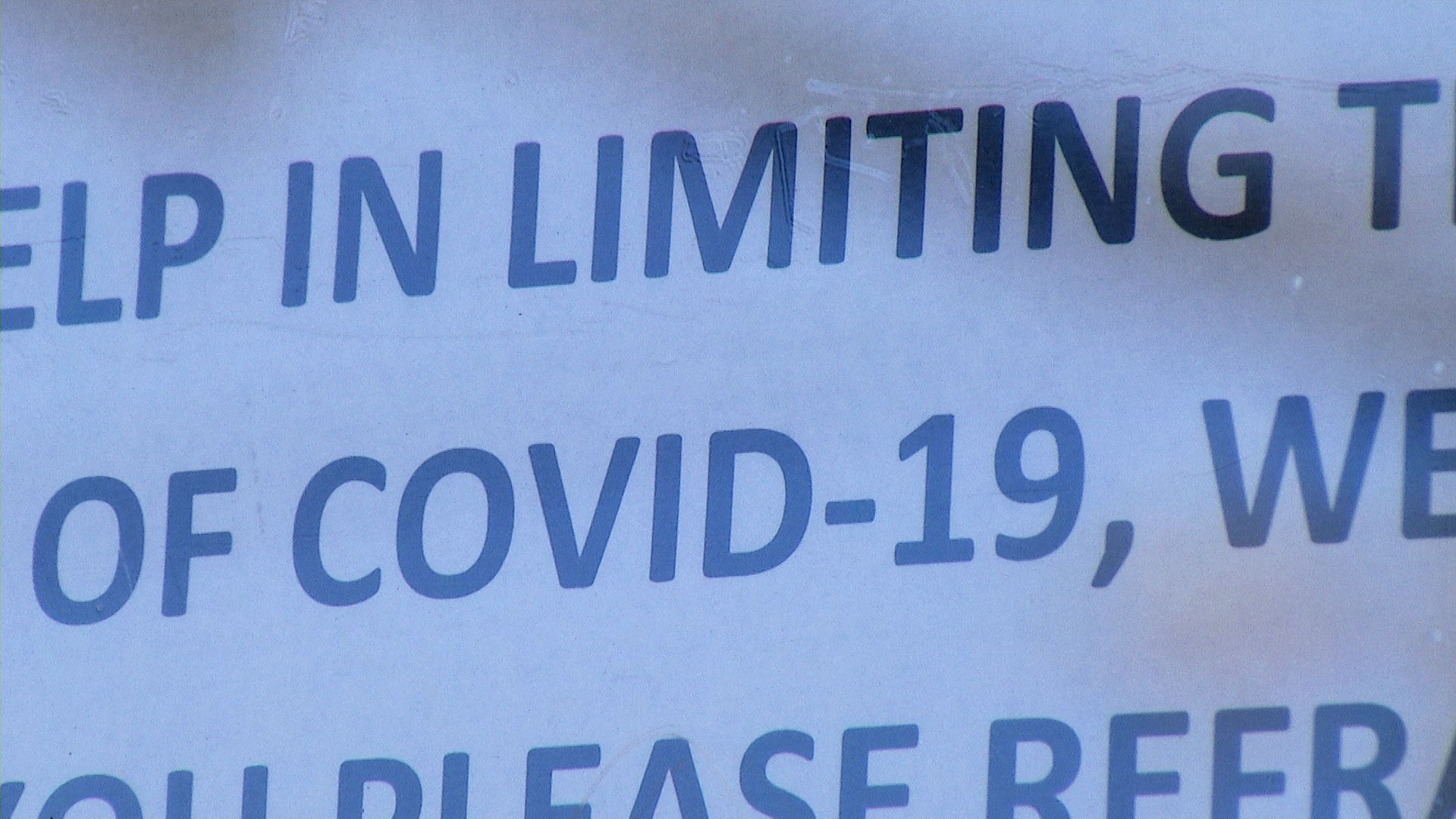 A closeup of a sign posted on a storefront in Tucson notifies customers of limited occupancy because of COVID-19.