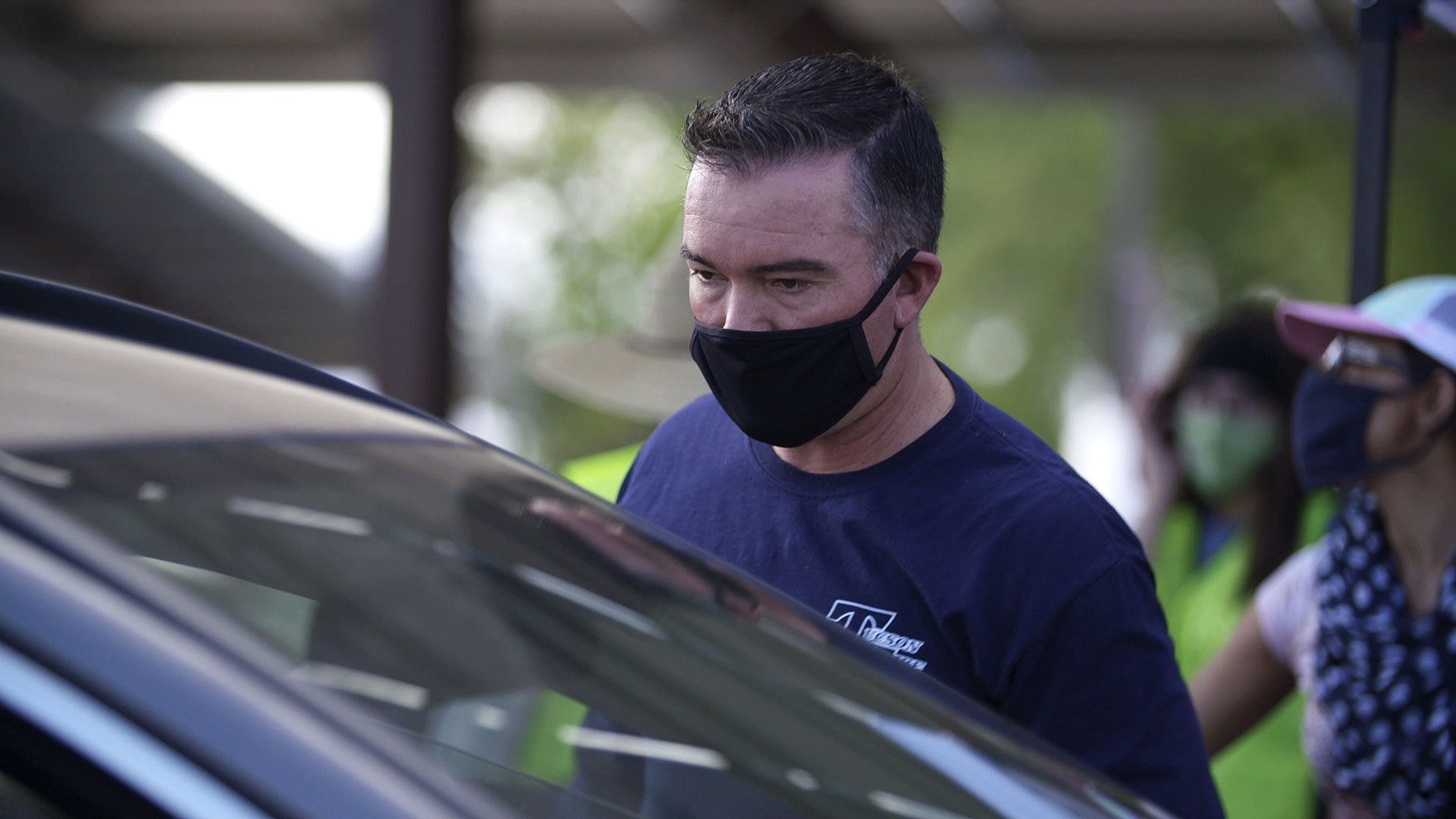 A member of the Tucson Fire Department helps distribute free masks at a giveaway event put on by the City of Tucson on July 18, 2020.