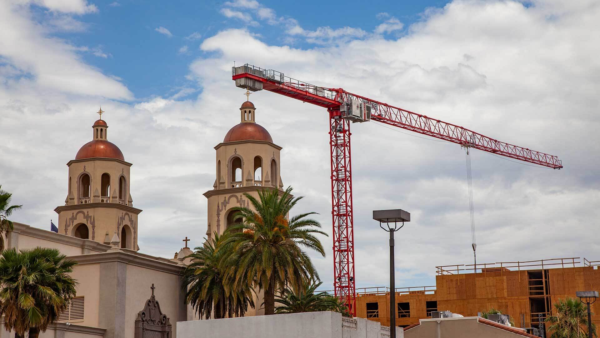 A crane rises above the construction site for a new Hilton Hotel across from the Cathedral St. Augustine.