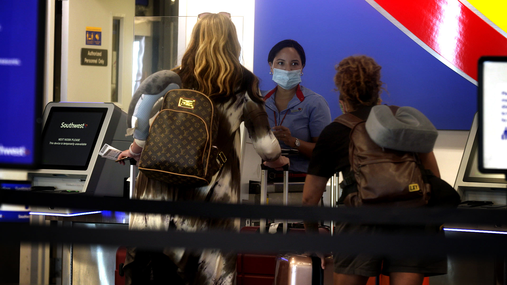 An employee for Southwest Airlines helps passengers at the ticket counter inside the Tucson International Airport on August 10, 2020.