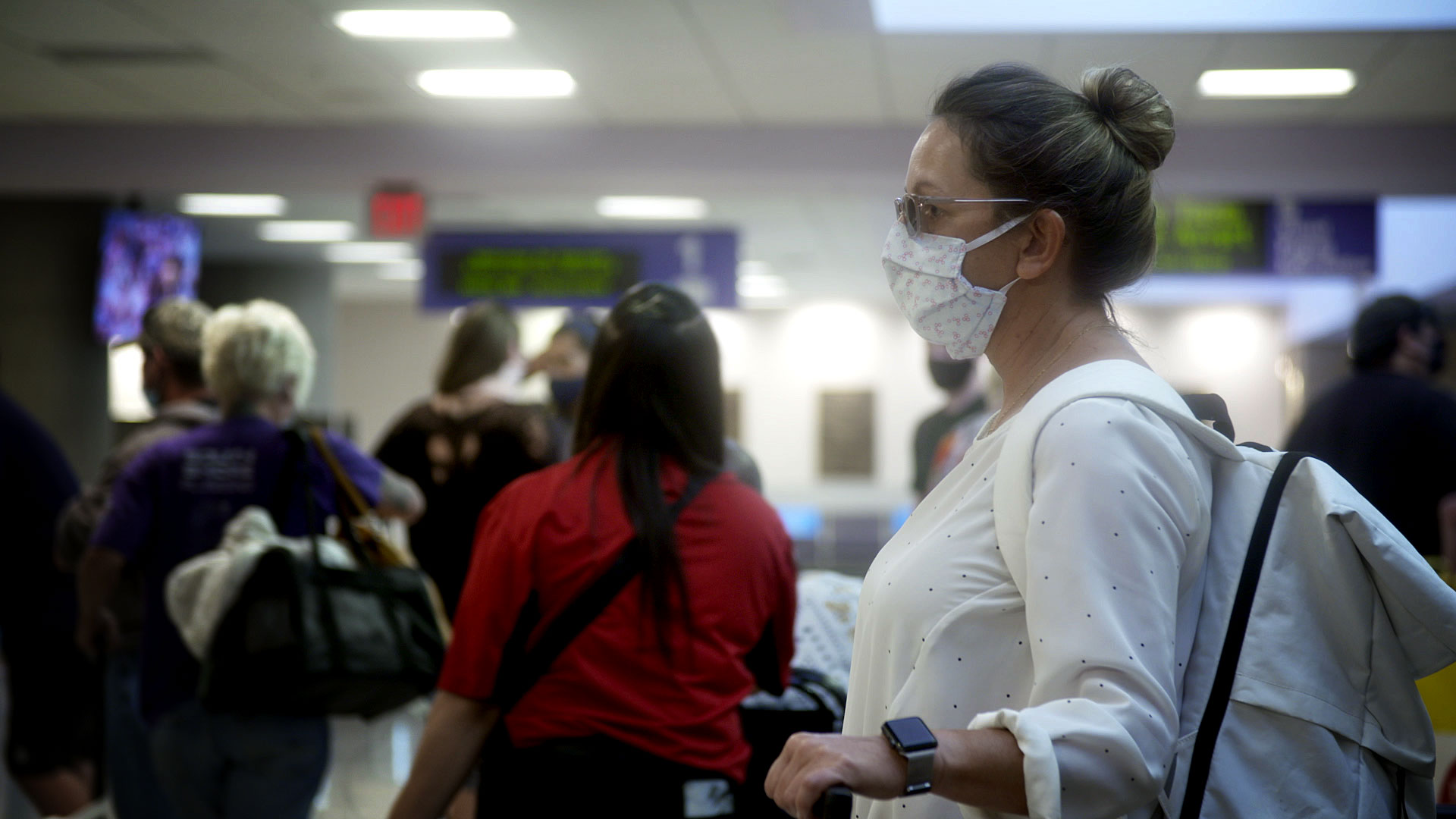 A woman stands with her luggage in the baggage claim area of the Tucson International Airport on August 10, 2020.