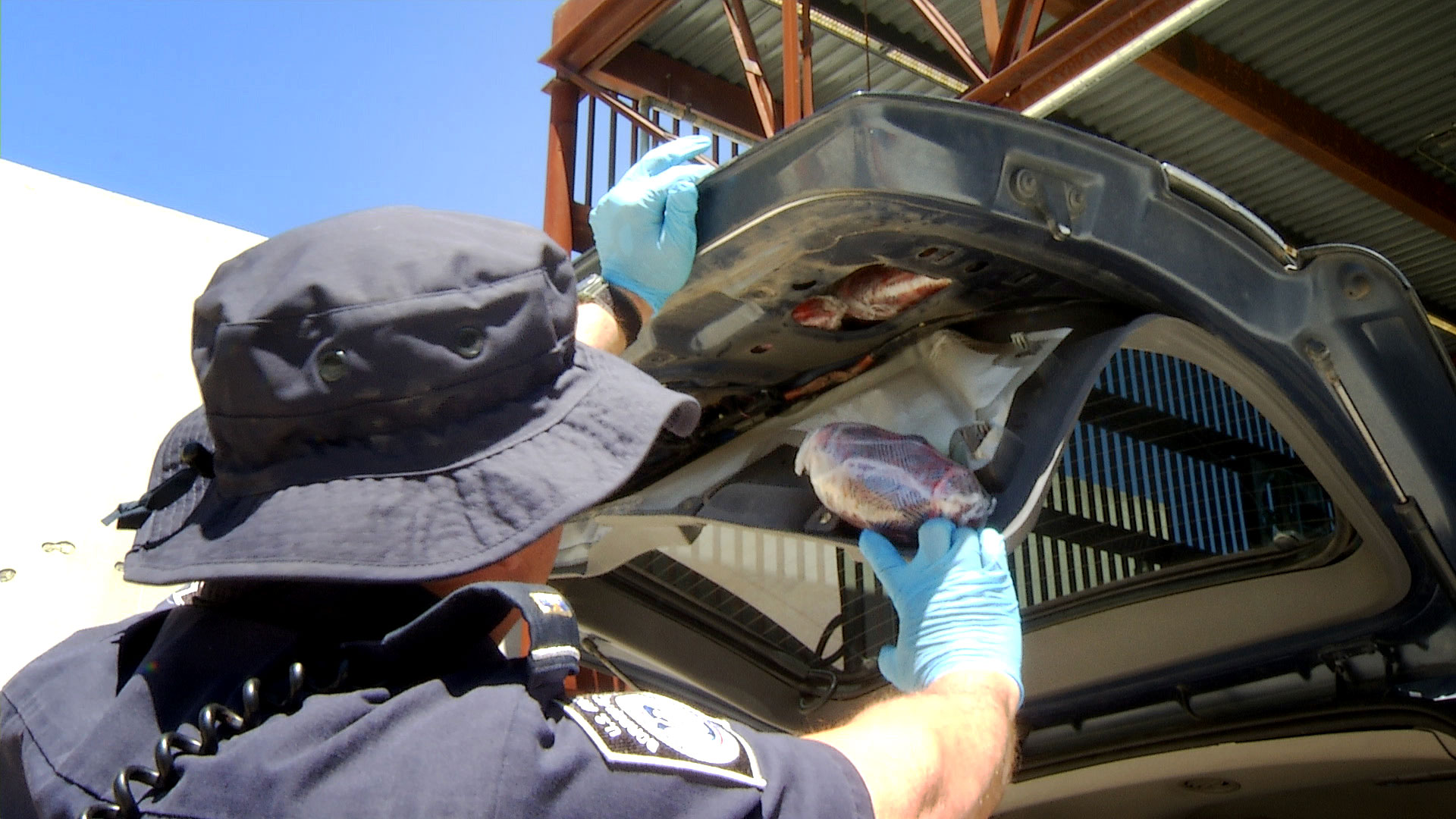 A customs officer removes packages of drugs hidden inside the rear door of an SUV at the Mariposa Port of Entry in Nogales. May 2019.