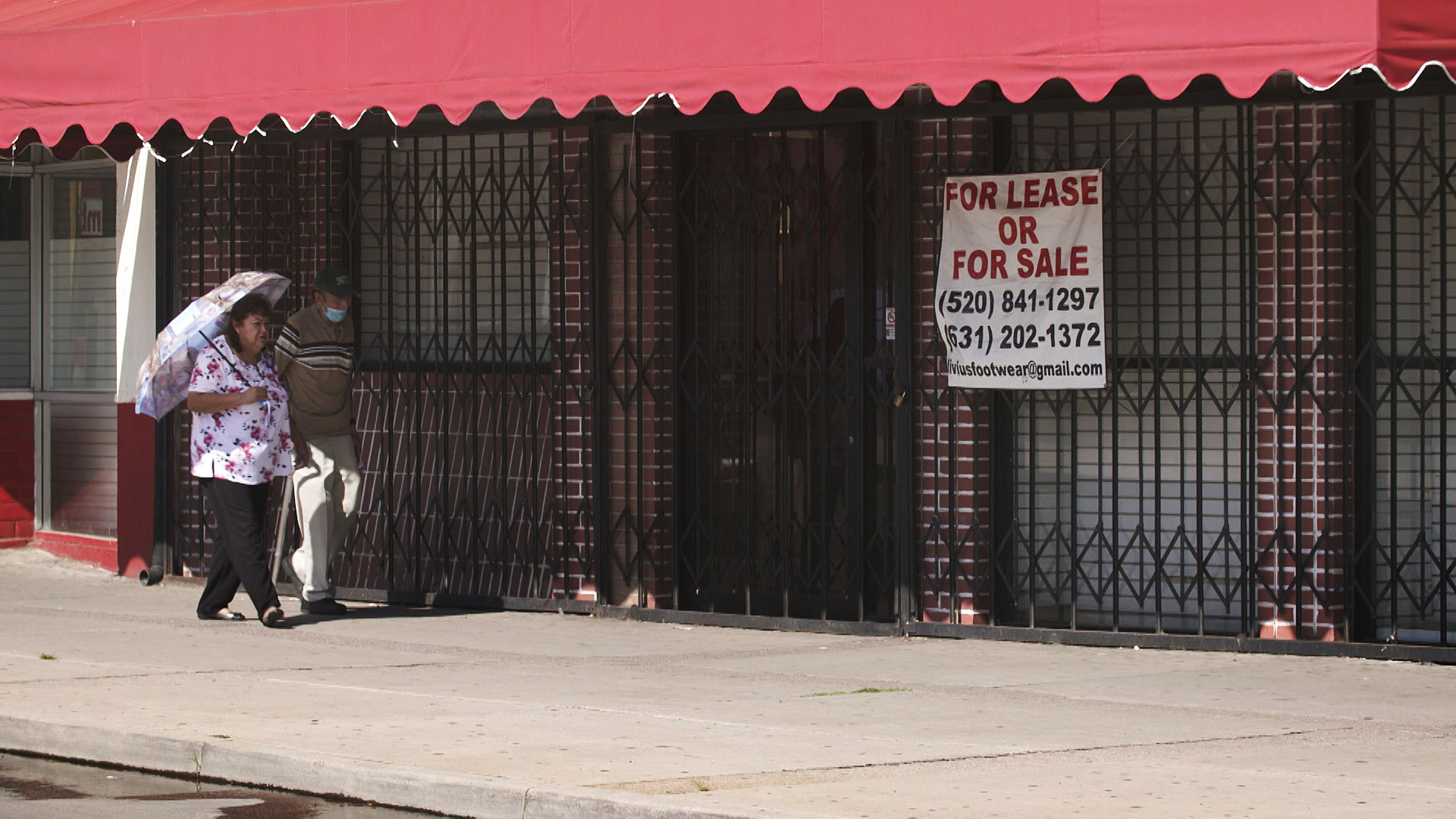 A man and woman walk past a closed building listed for sale in Nogales, Arizona on August 17, 2020.