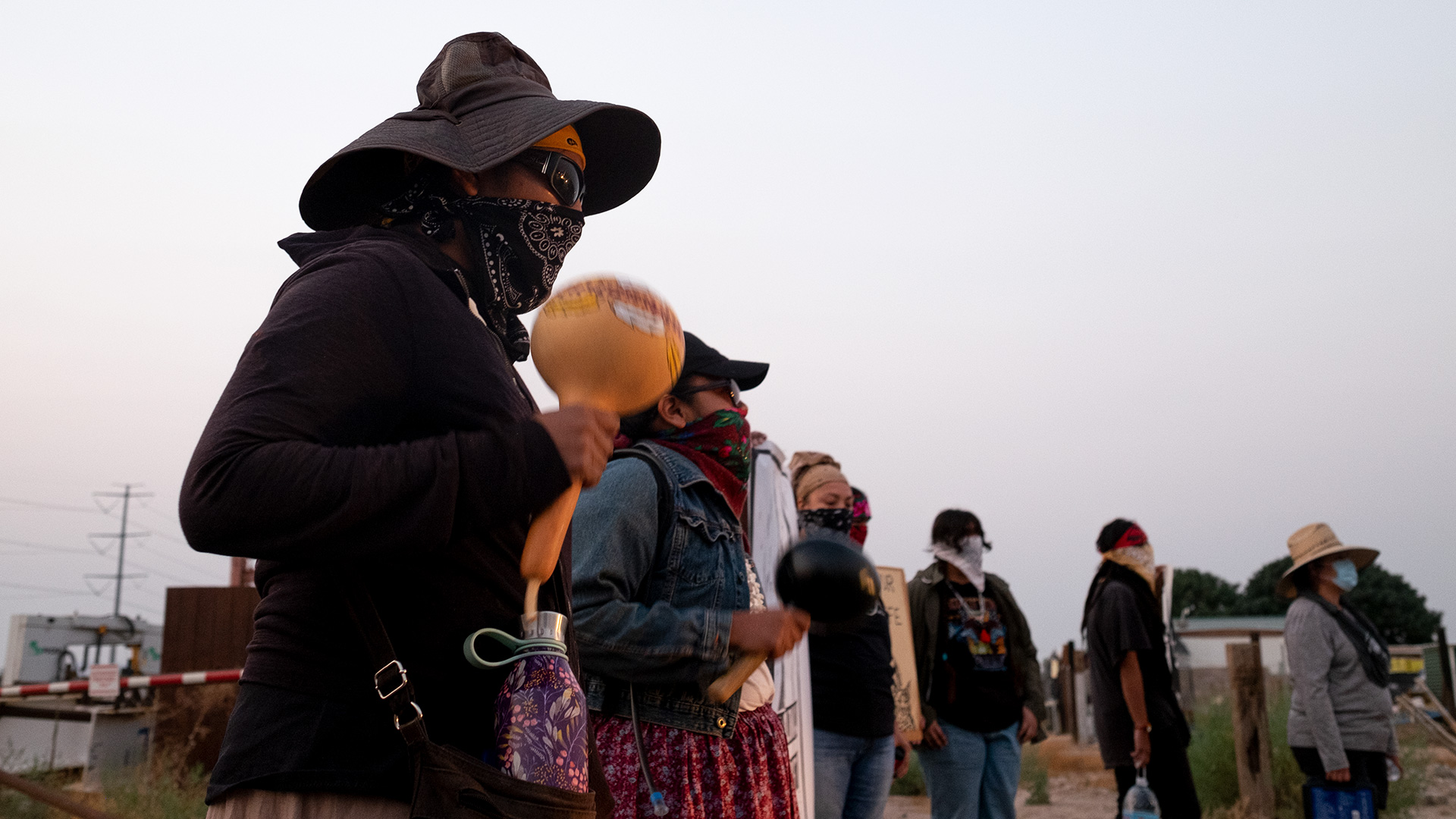 An Indigenous demonstrator shakes a rattle during the early morning protest in Coolidge on Aug. 26, 2020.