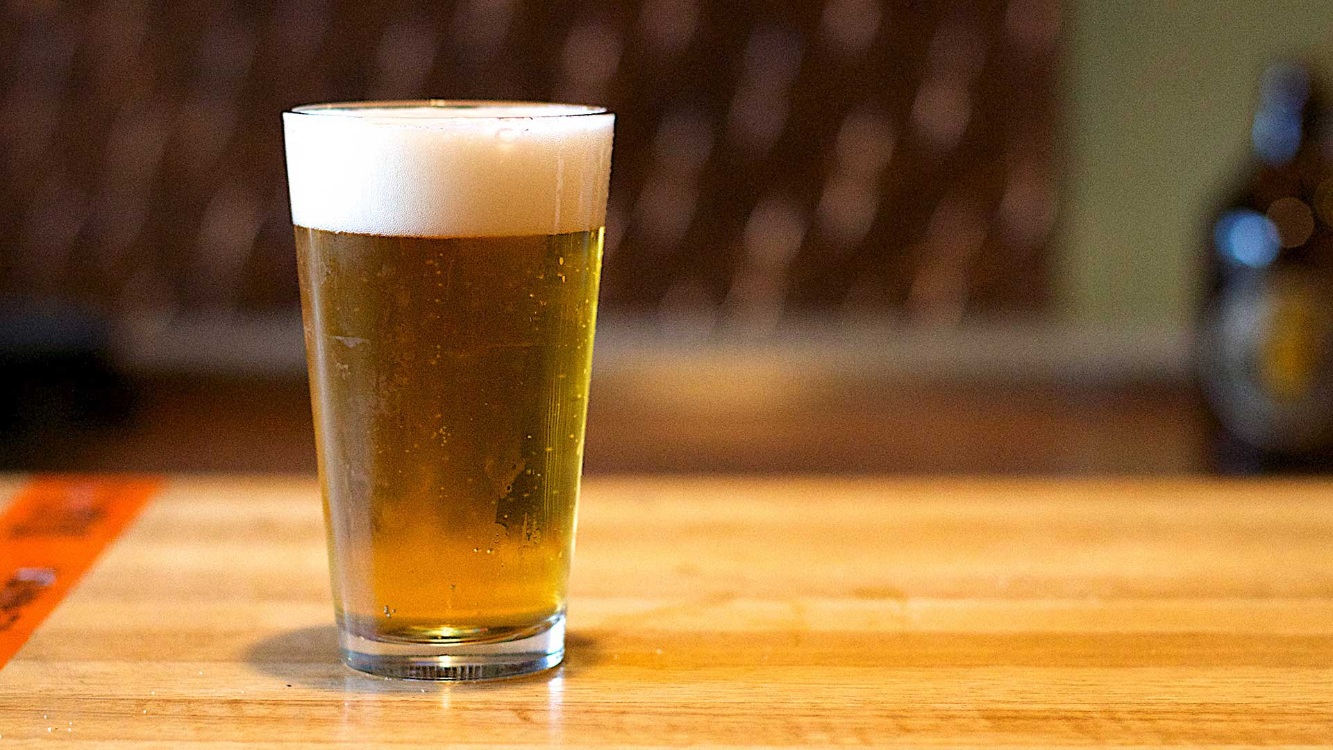 A glass of beer on a table.