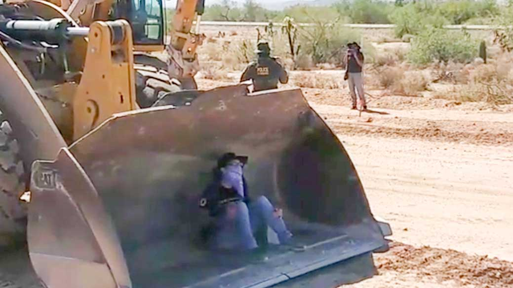 A Hia-Ced O'odham protester sits inside a vehicle to block construction on a stretch of border wall going up in Organ Pipe Cactus National Monument on Sept. 9, 2020.