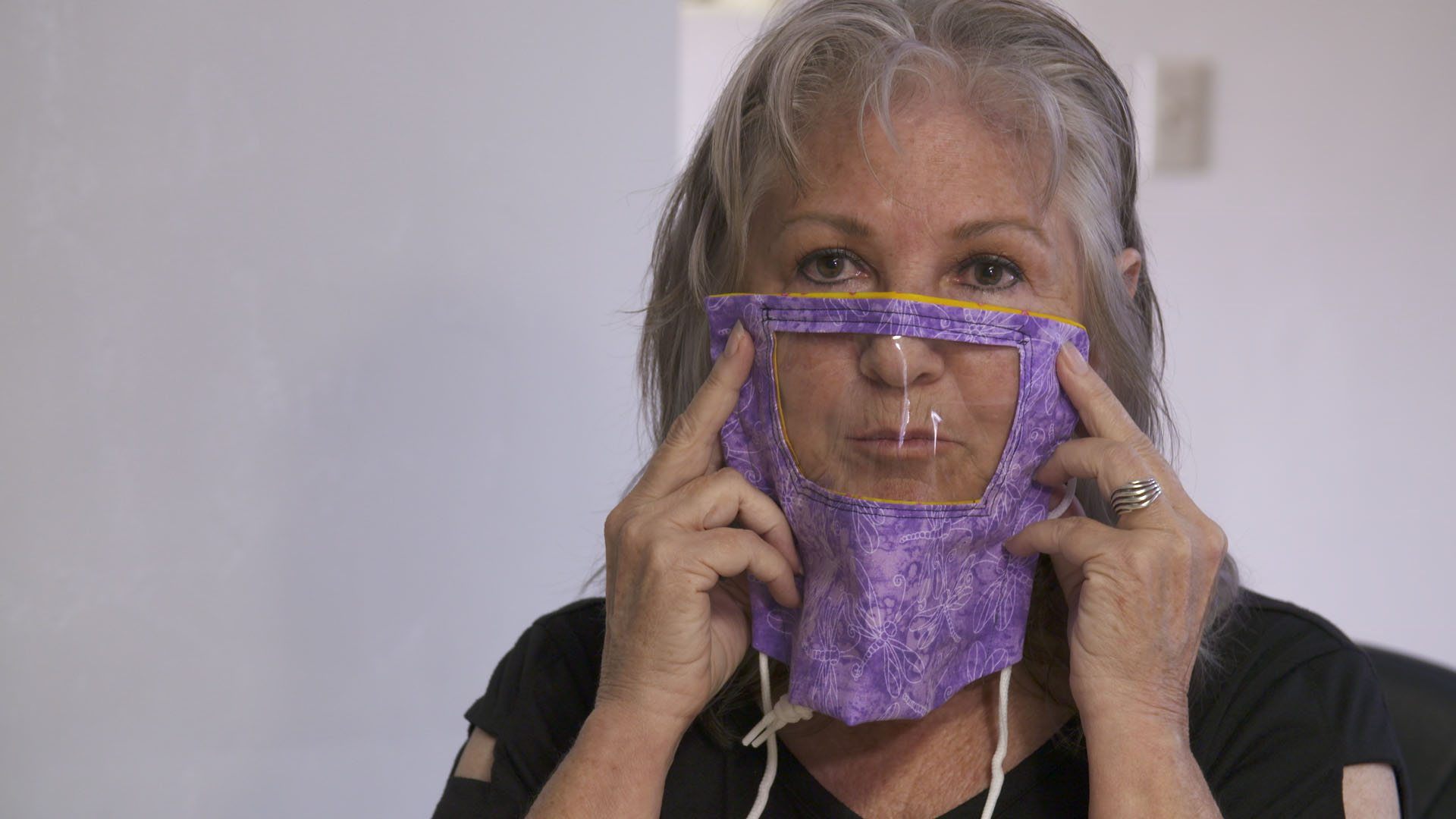 Terri Rice with Adult Loss of Hearing Association demonstrates how to wear a mask she designed to increase lip reading abilities.