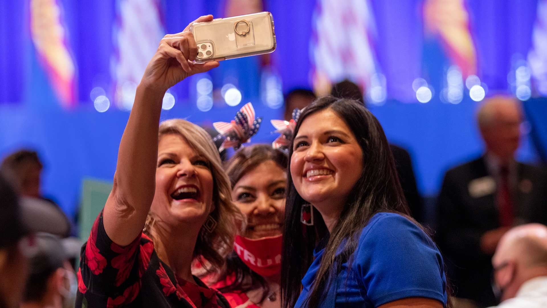 Arizona Republican Party Chairwoman Kelli Ward snaps a selfie with supporters of President Donald Trump at a Latinos for Trump event in Phoenix, Monday, Sept. 14. Like Ward, most of those attending the roundtable were maskless.