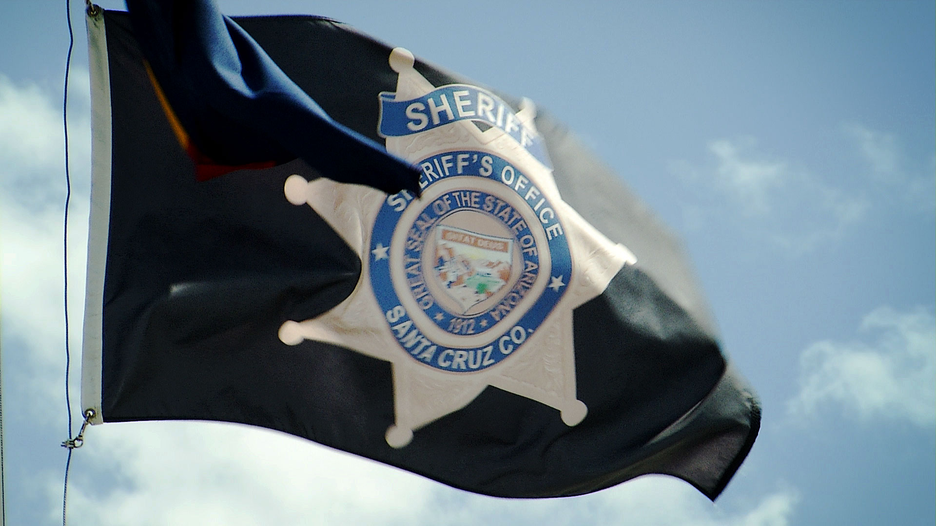 A flag for the Santa Cruz County Sheriff's Department outside of the department's headquarters in Nogales, Arizona.