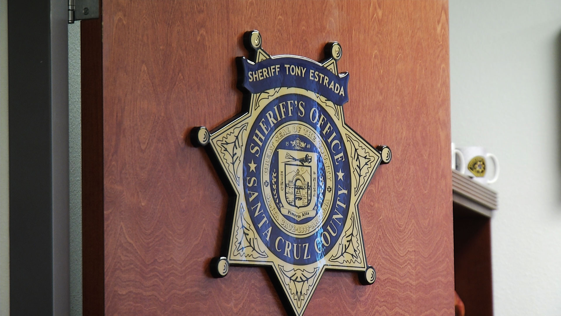 A sheriff's star sign hangs on the door of Santa Cruz County Sheriff Tony Estrada's office at the department in Nogales.