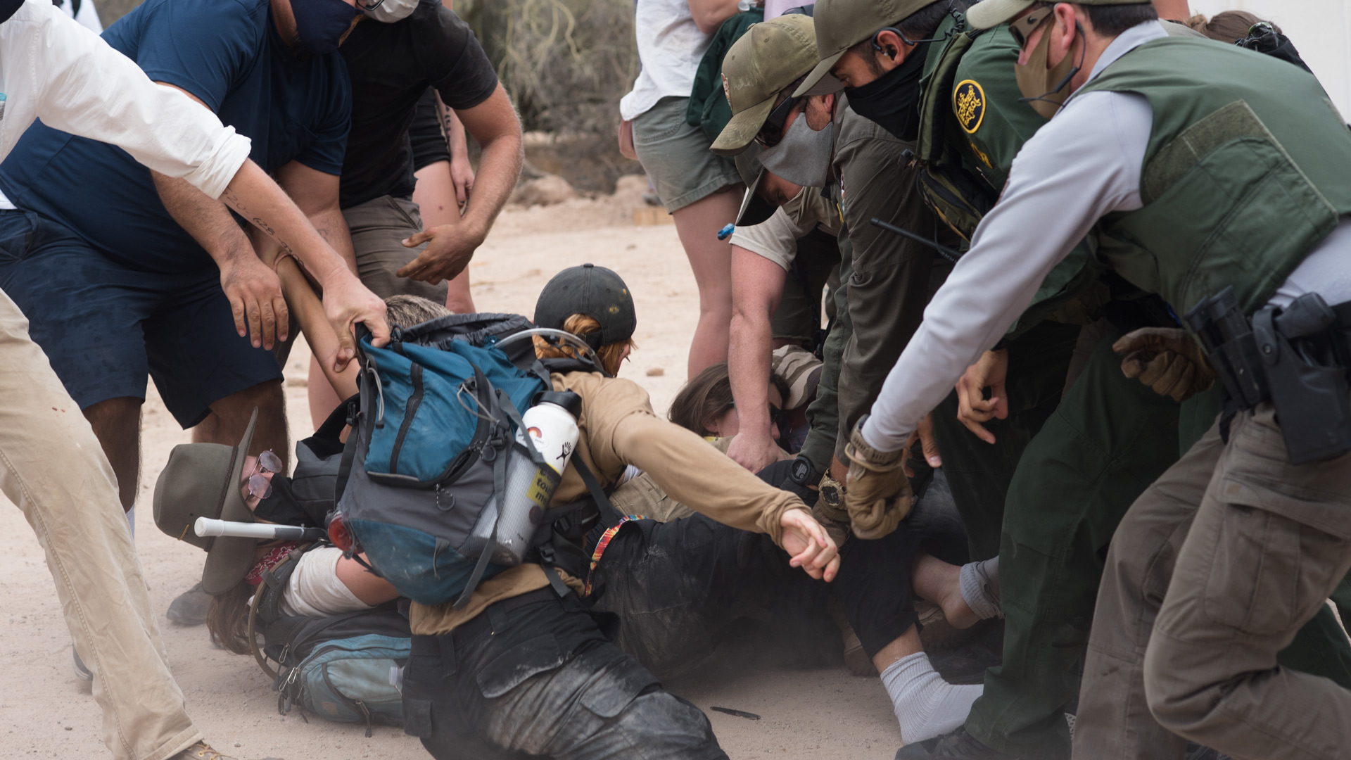 Demonstrators struggle as National Park Service officers and Border Patrol agents try to pull people from a fallen human chain during a demonstration at Organ Pipe Cactus National Monument on Sept. 21, 2020.