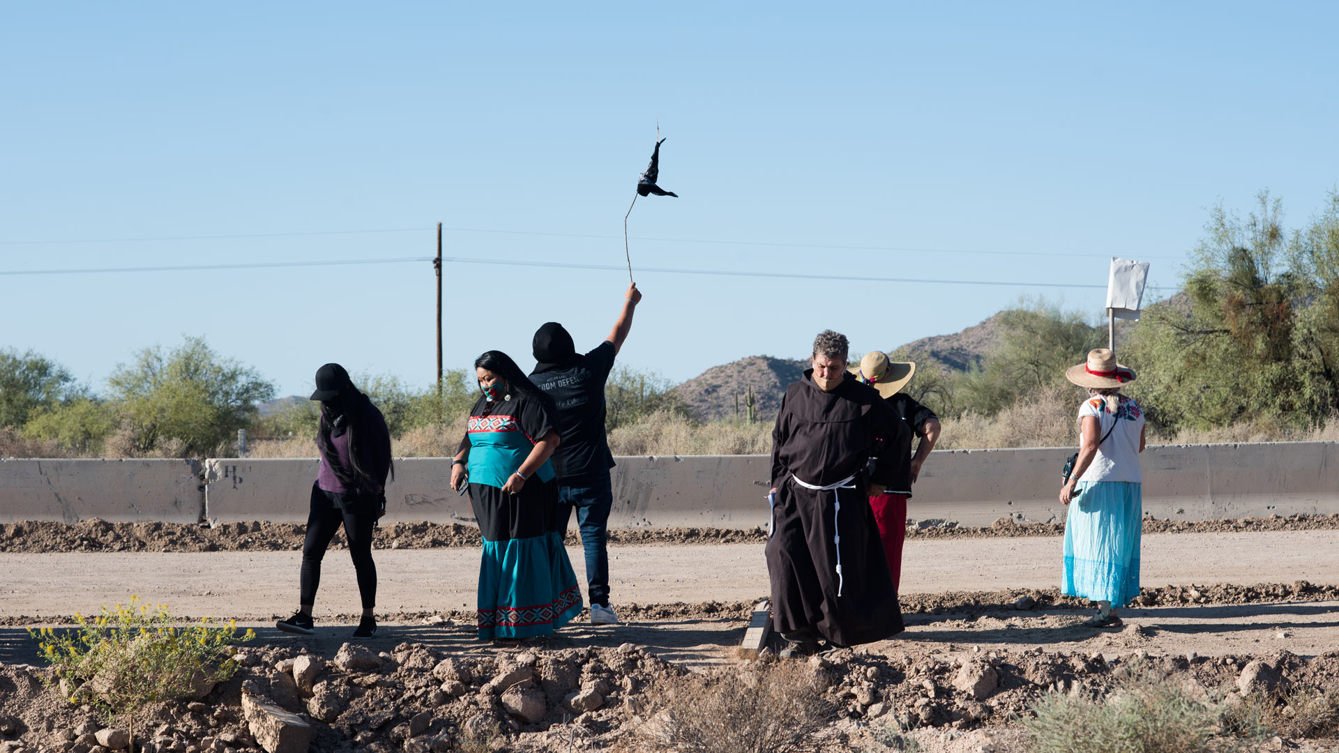 Tribal members and supporters gather in front of the construction line to wave down O'odham runners coming from Sonora ahead of a cross-border ceremony at Quitobaquito Springs on Sept. 27, 2020.