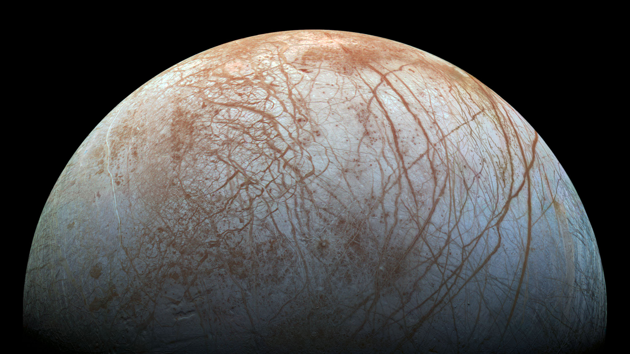 "Composed of images taken by the Galileo spacecraft in 1995 and 1998, this reprocessed image of the icy Jovian moon Europa shows cracks, ridges, ""microchaos,"" and more. We now believe that Europa, like several other moons in the solar system, is an ocean world. Due to heat caused by Jupiter's gravitational push-and-pull, there is liquid salt water beneath the ice, water that may contain life."