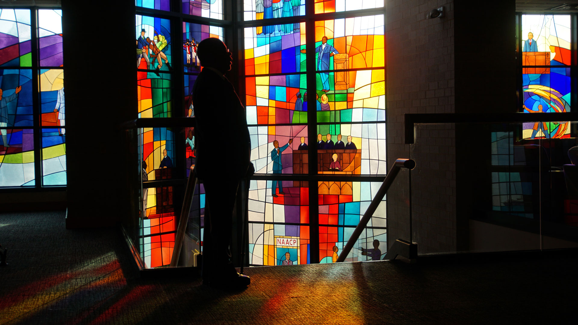 Host, Henry Louis Gates Jr. standing in front of stained glass at Trinity United Church of Christ in Chicago.