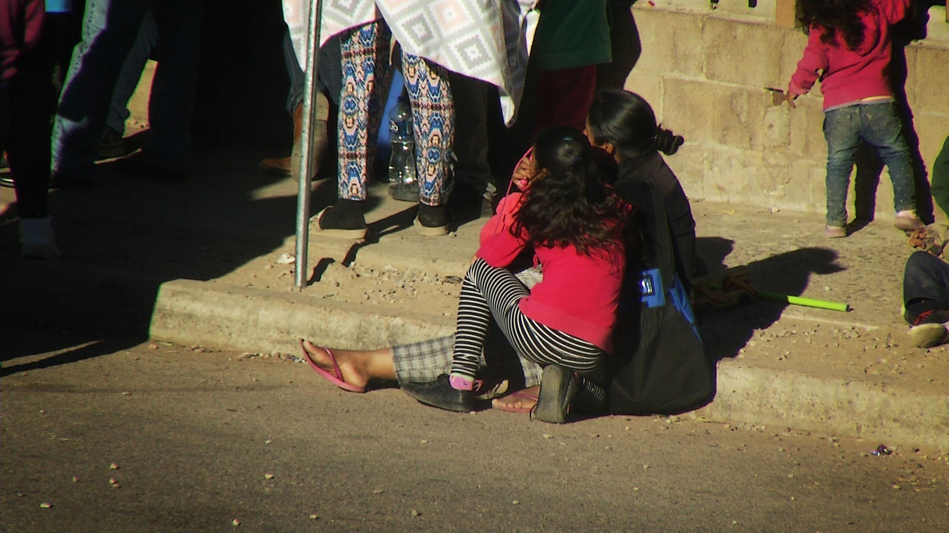 A woman and girl sit on the sidewalk with a group of migrants as they wait to enter the Kino Border Initiative's cafeteria. The nonprofit provides humanitarian aid to migrants and deportees in Nogales, Sonora. February 2020.
