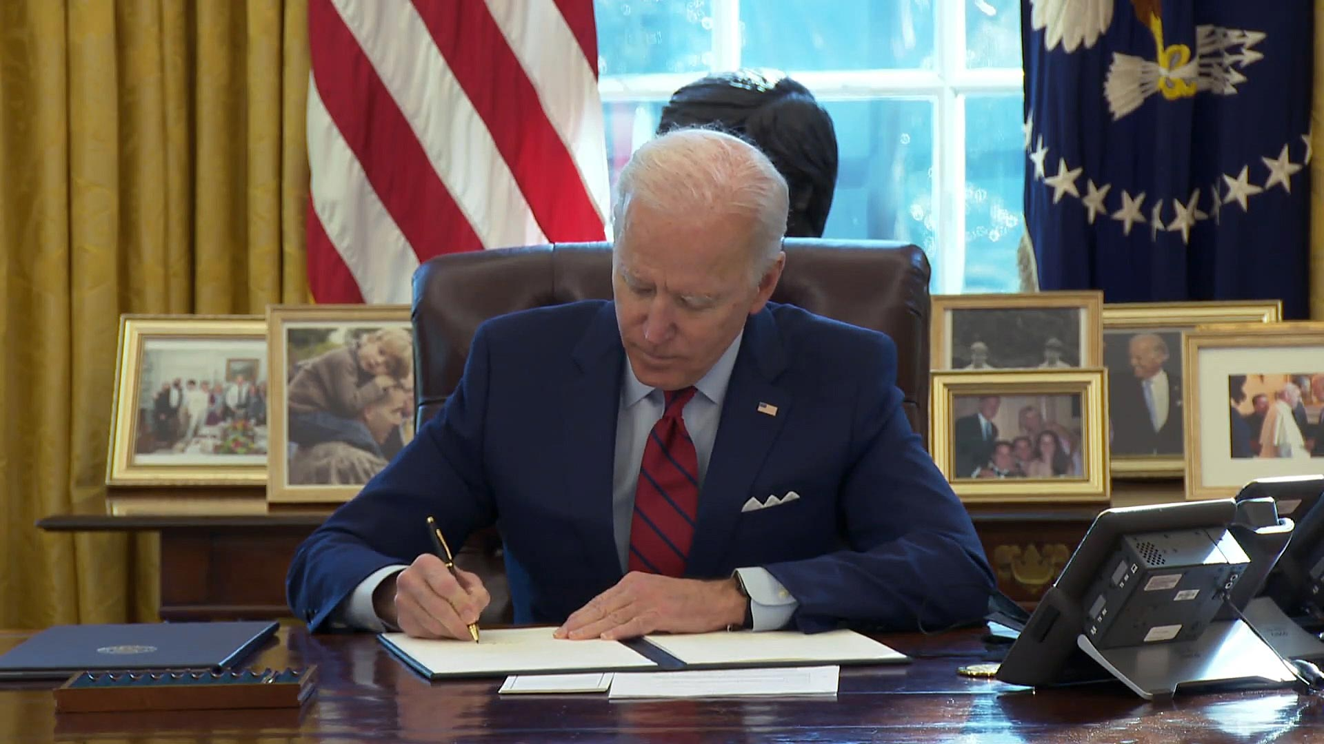 President Joe Biden signs executive orders at his desk in the Oval Office on Jan. 28, 2021.