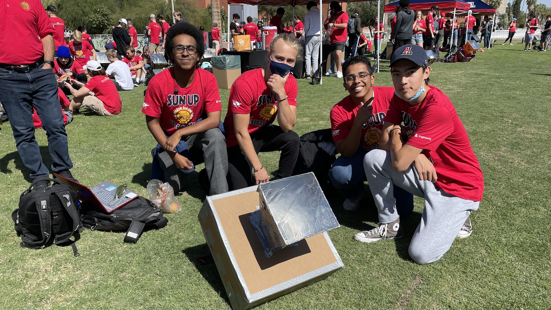 """University of Arizona Engineering students Joseph White, Levi Mccluskey, Osamah Bahamid and Eric Anthony Pineda pose in front of their solar oven on Wednesday, October 13th, 2021, as part of the school's annual """"Solar Oven Throwdown"""" event."""
