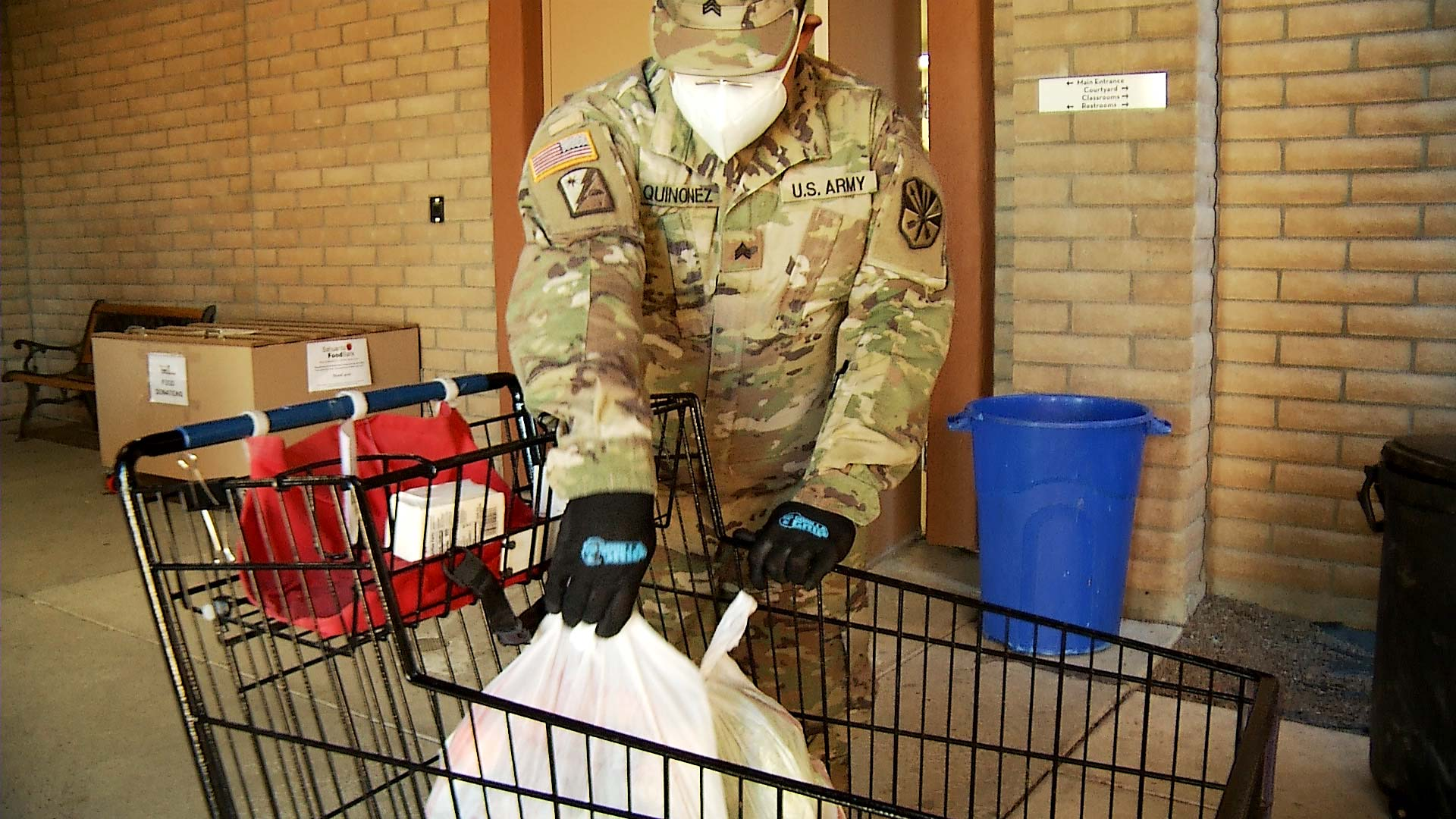 A guardsman with the Arizona National Guard loads groceries in a cart at a food bank in Sahuarita on Feb. 11, 2021.