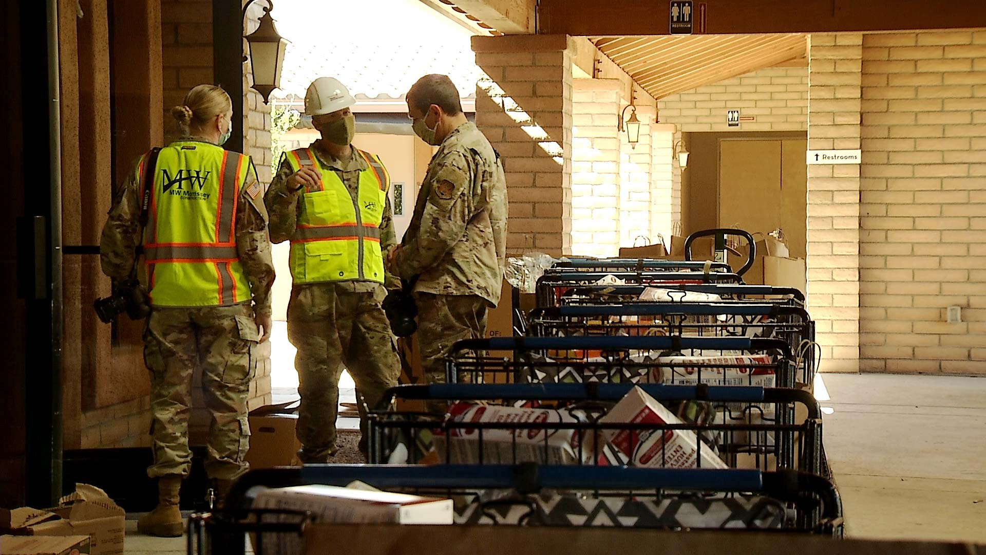 Members of the Arizona National Guard converse near a row of shopping carts at a food bank in Sahuarita on Feb. 18, 2021.