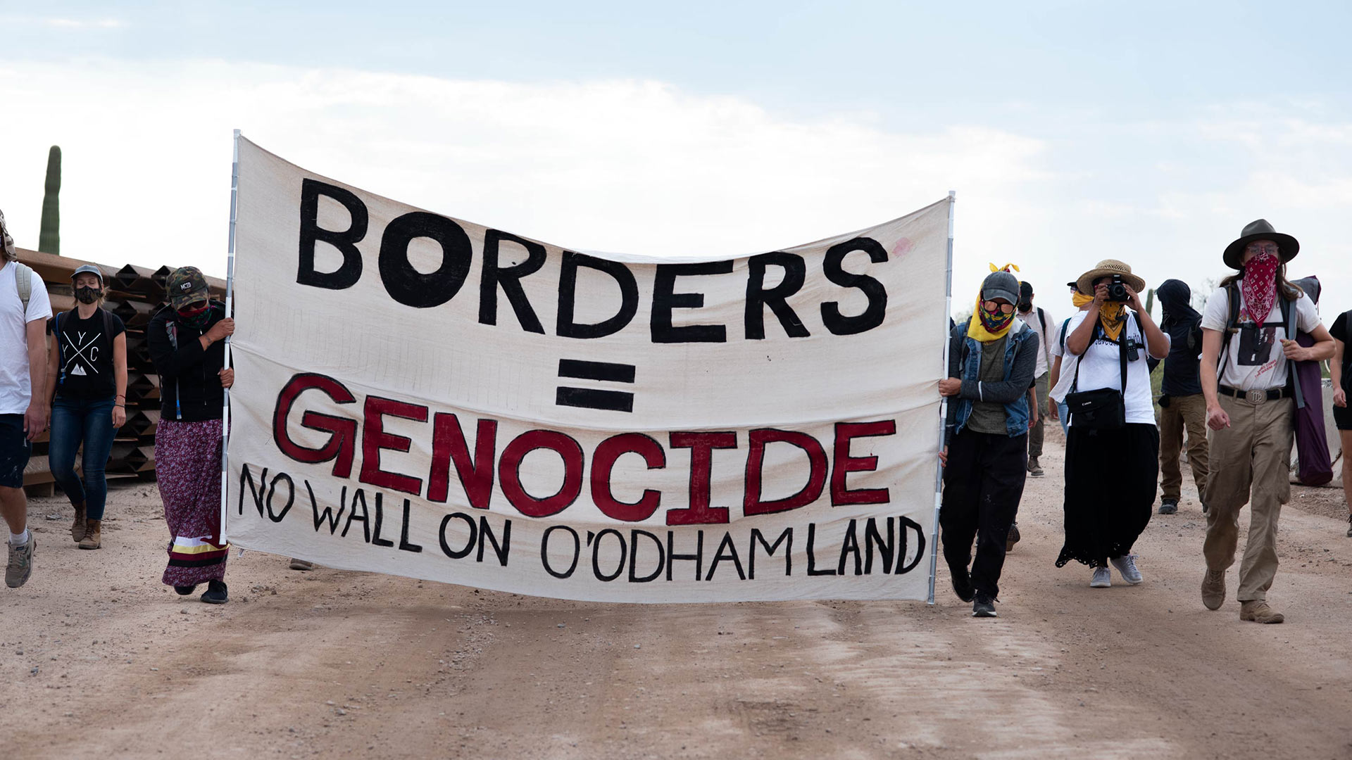 Indigenous-led protesters walk along a construction line in Organ Pipe Cactus National Monument in Sept. 2020.