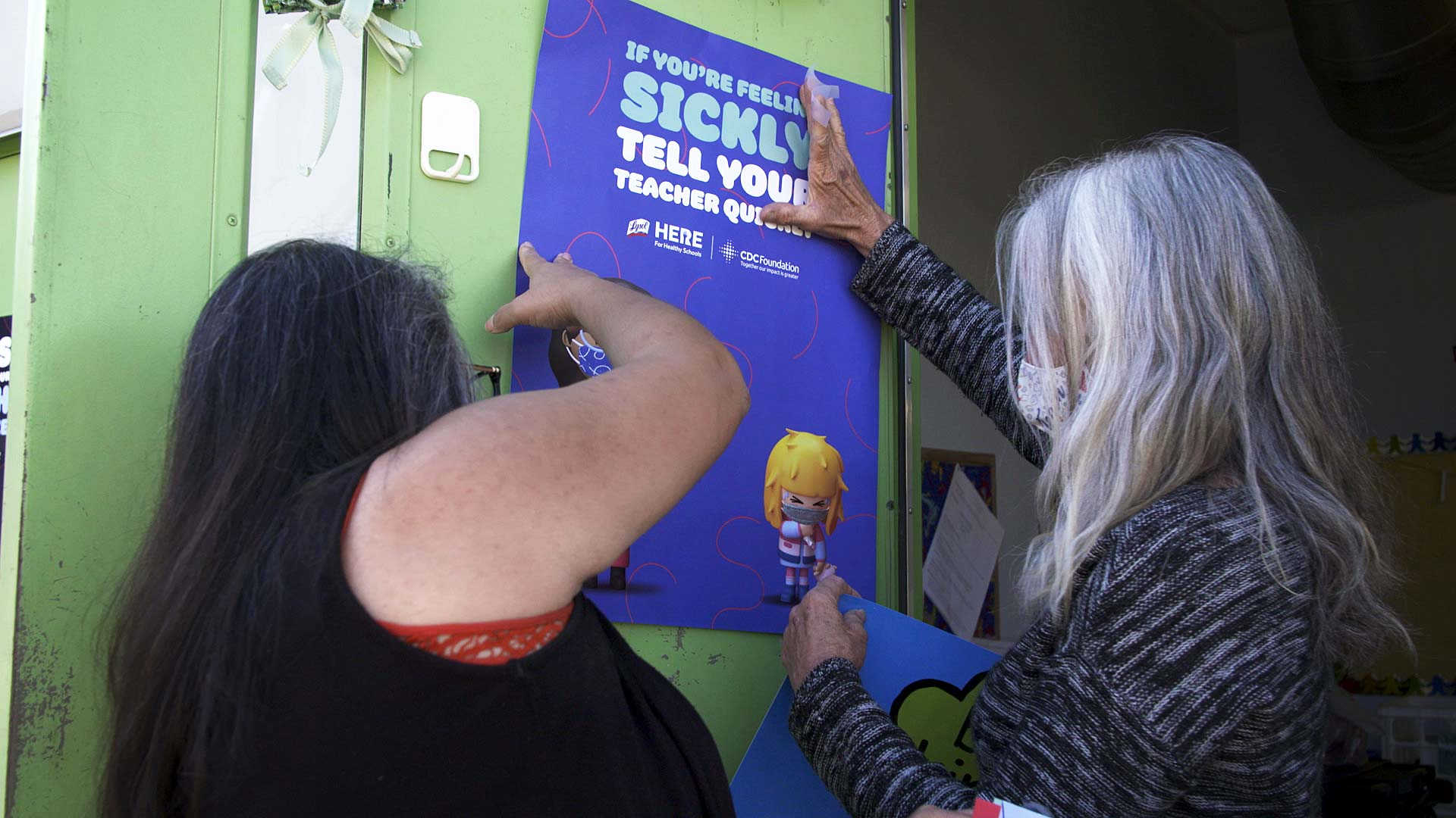 Staff at Davidson Elementary in the Tucson Unified School District hang a poster letting students know to report if they feel sick. March 10, 2021.