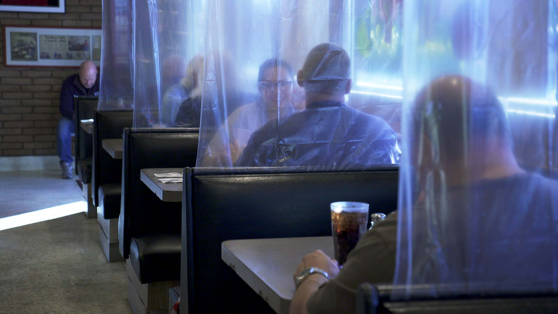 Plastic separates booths as customers dine at Gus Balon's Restaurant in Tucson. November 2020.