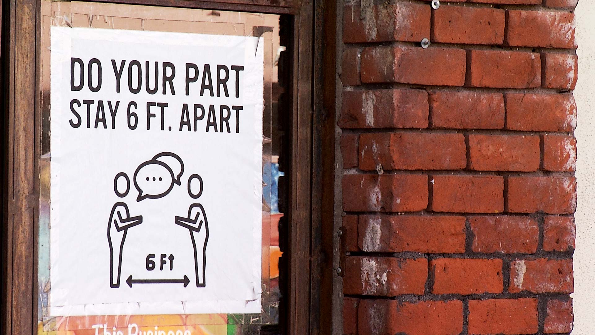 A sign taped to the window of a business in Tucson reminds people to stay 6 feet apart. 2020.