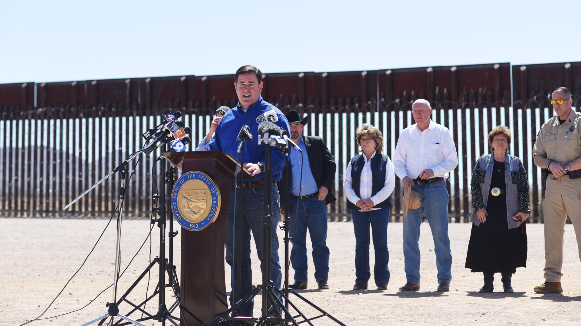 Governor Doug Ducey addresses members of the media in front of a portion of border wall near the Douglas Municipal Airport on March 19, 2021.