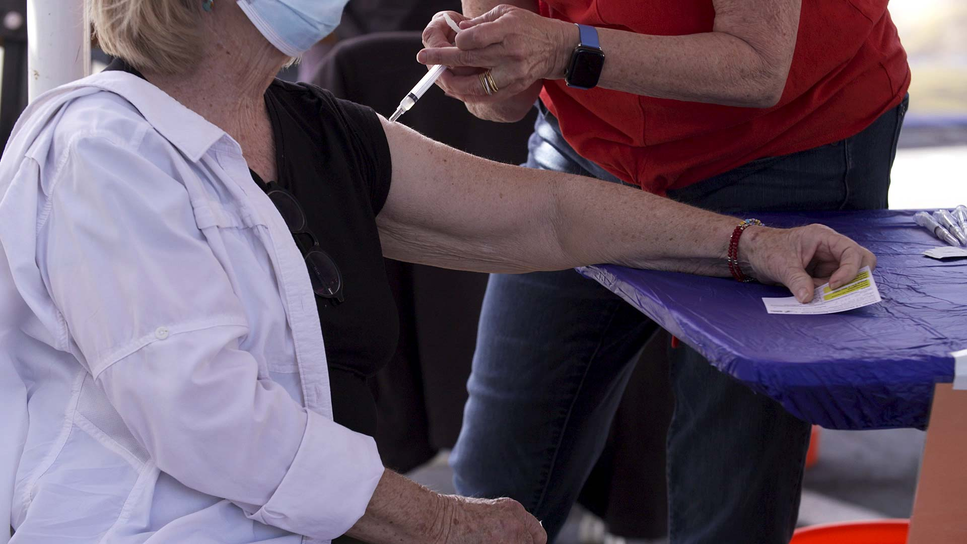A woman receives a COVID-19 vaccine during a mobile event run by Pima County and Tucson Medical Center outside St. John the Evangelist Catholic Church on March 6, 2021.