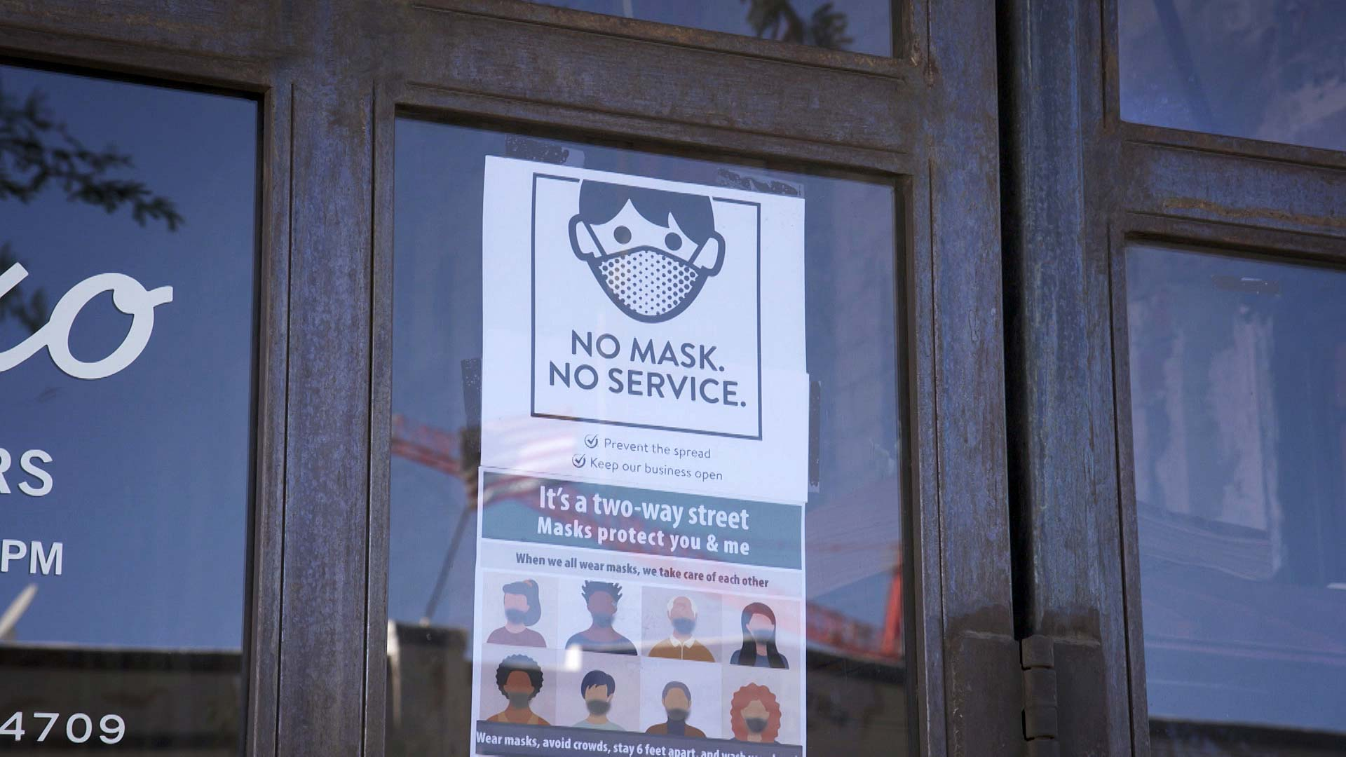 A poster on the storefront of Tap and Bottle in Tucson informs customers that masks are required to enter. January 2021.