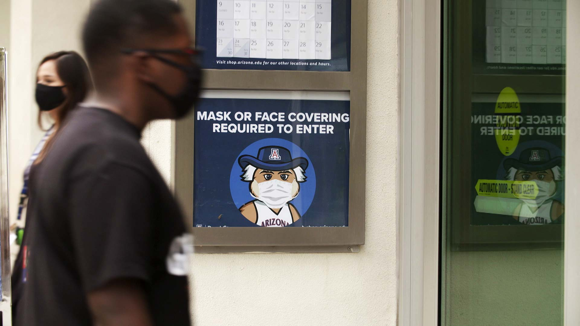 A sign outside of the University of Arizona bookstore reminds visitors that masks are required to enter.