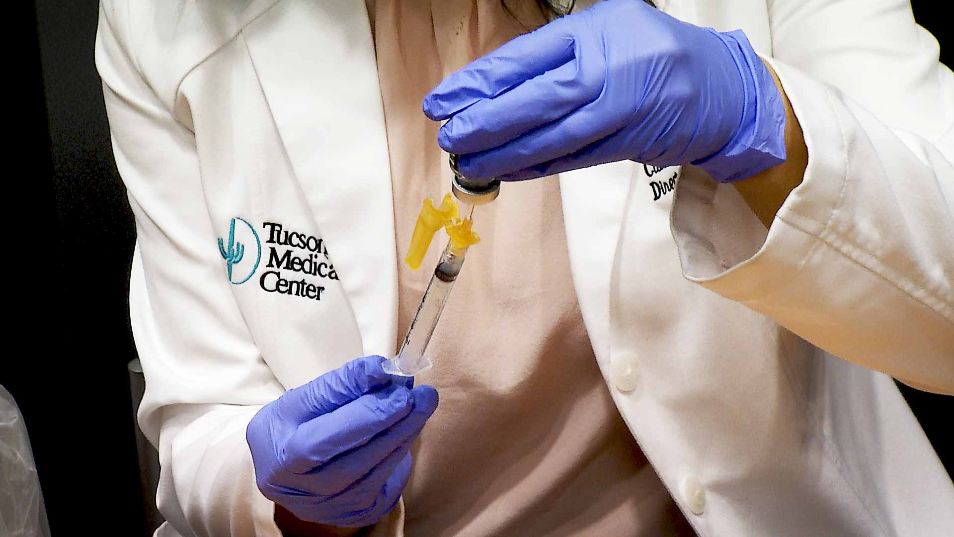 A health care worker at Tucson Medical Center fills a syringe with a dose of the COVID-19 vaccine. January 2021.