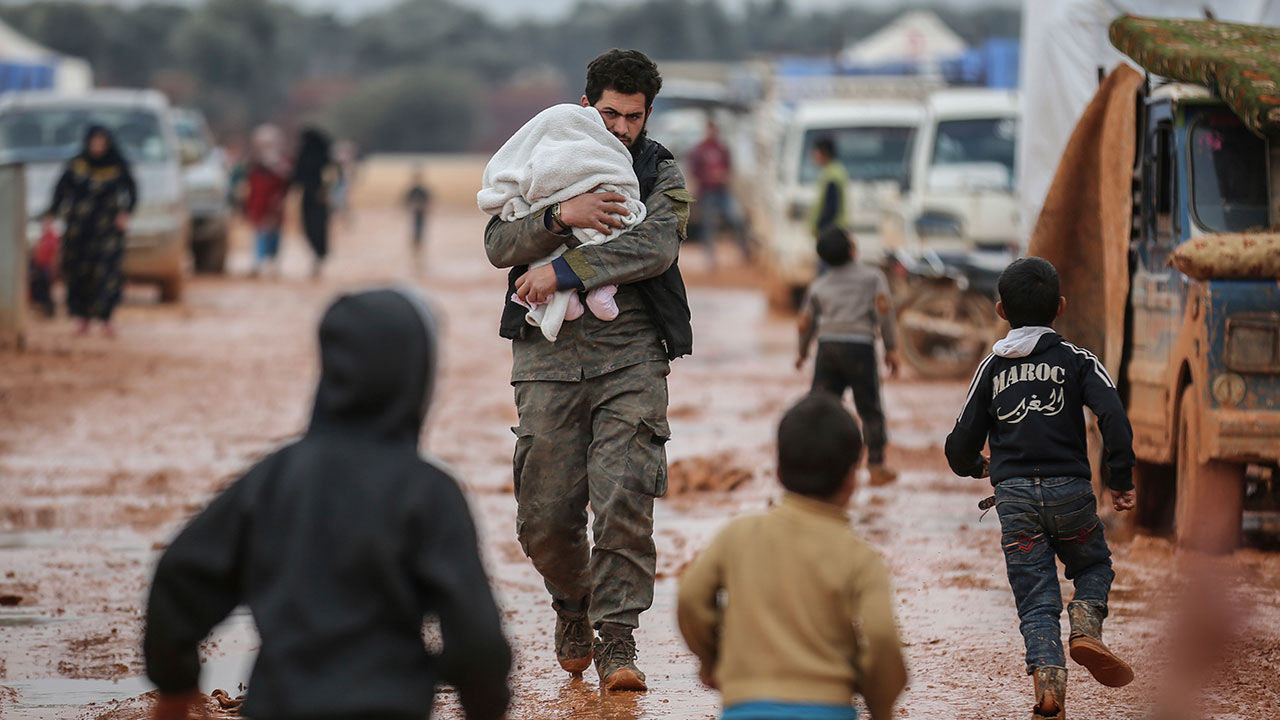 A Syrian man carries his baby at a makeshift camp for families displaced from Idlib countryside as a result of the bombing and military operations on Feb. 18, 2020.