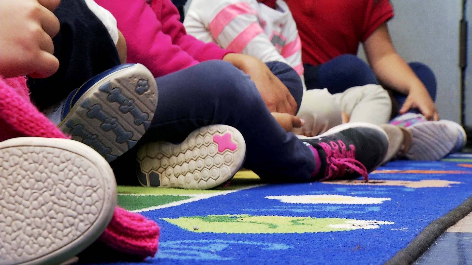 The shoes of children as they sit in a row inside a kindergarten classroom.
